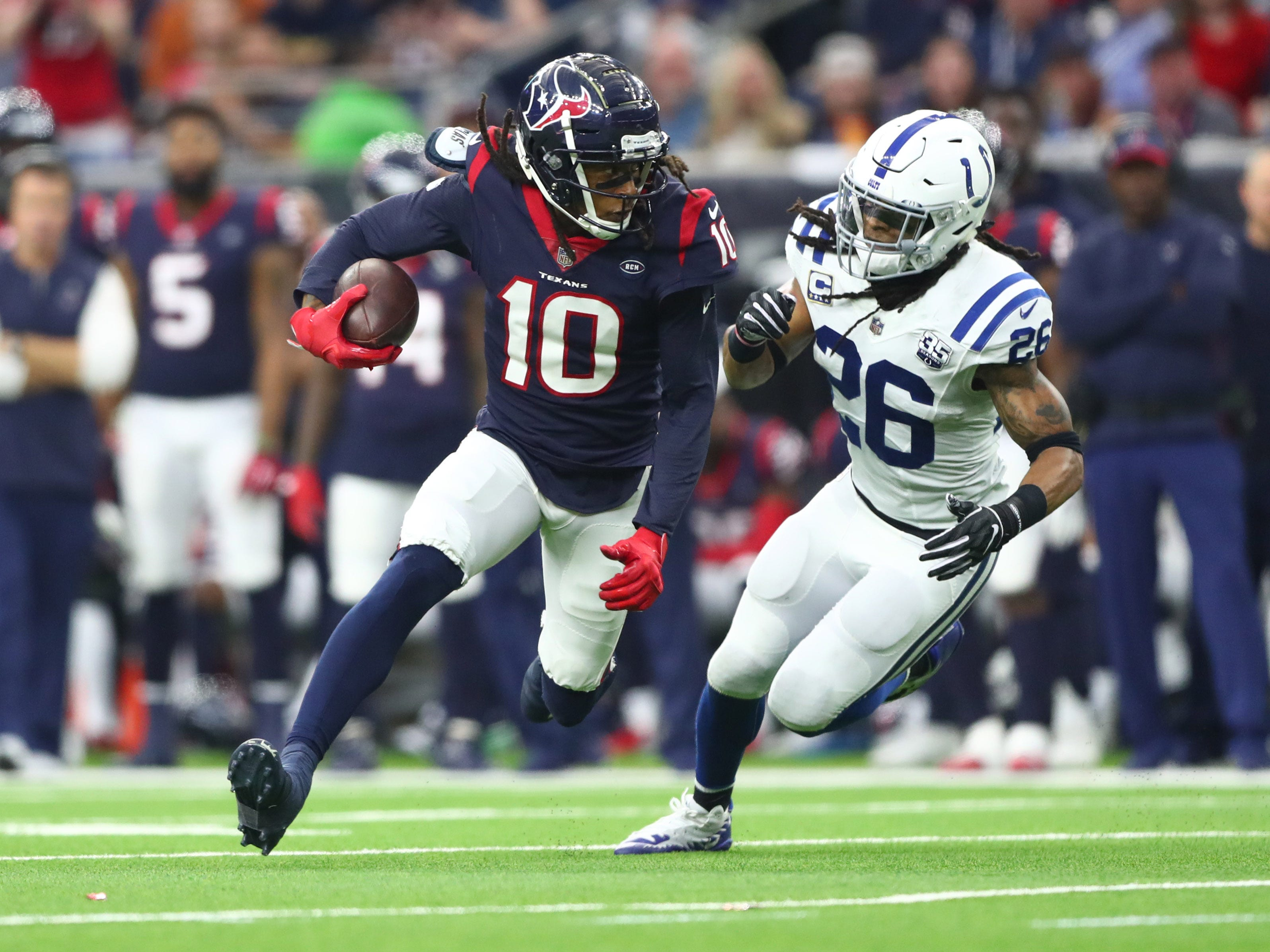 Houston Texans wide receiver DeAndre Hopkins (10) is chased by Indianapolis Colts strong safety Clayton Geathers (26)  in the second quarter in a AFC Wild Card playoff football game at NRG Stadium.