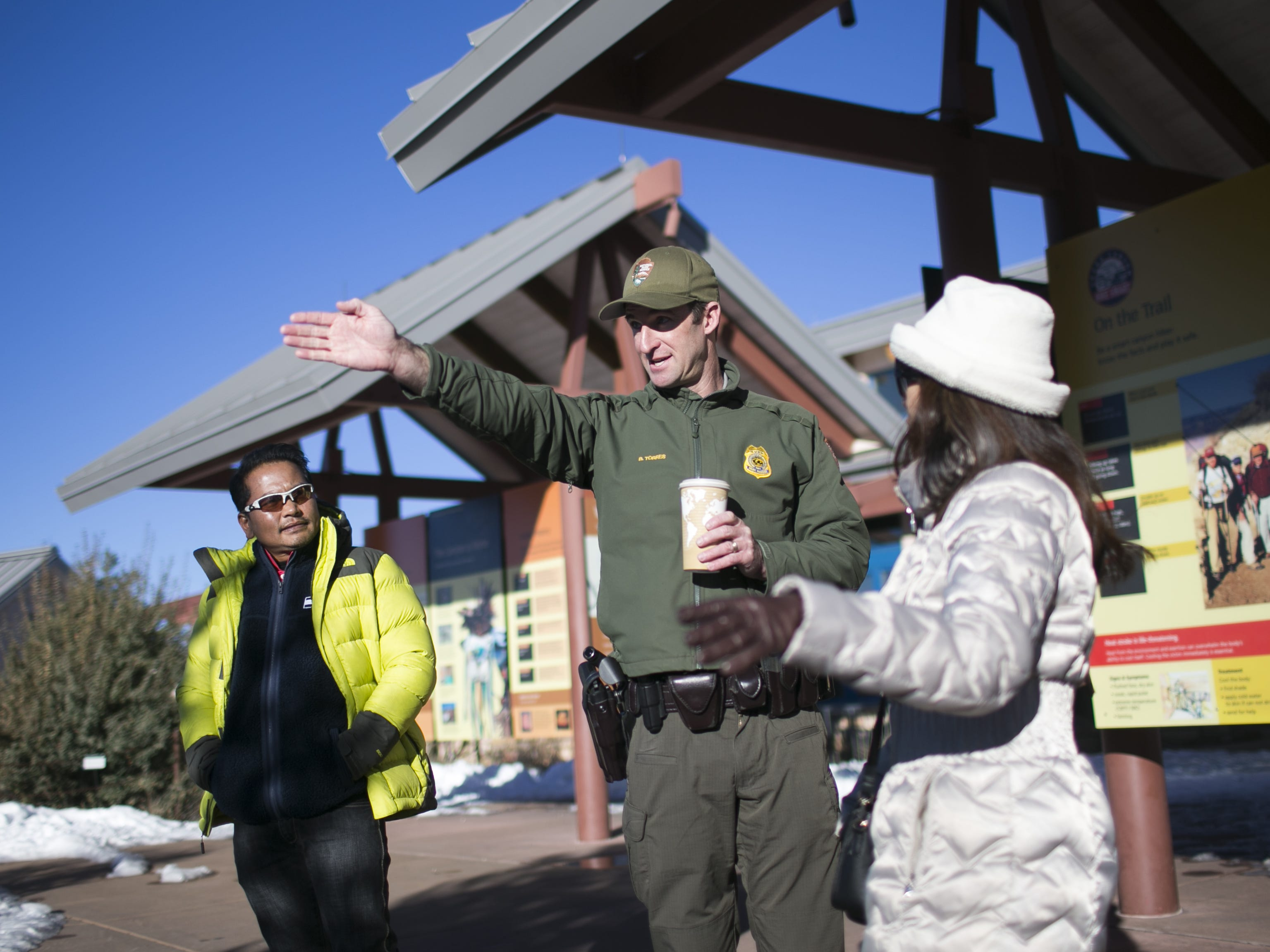 Brandon Torres, center, the Branch Chief of Emergency Services at Grand Canyon National Park, directs guests in the park on Jan. 4, 2019.