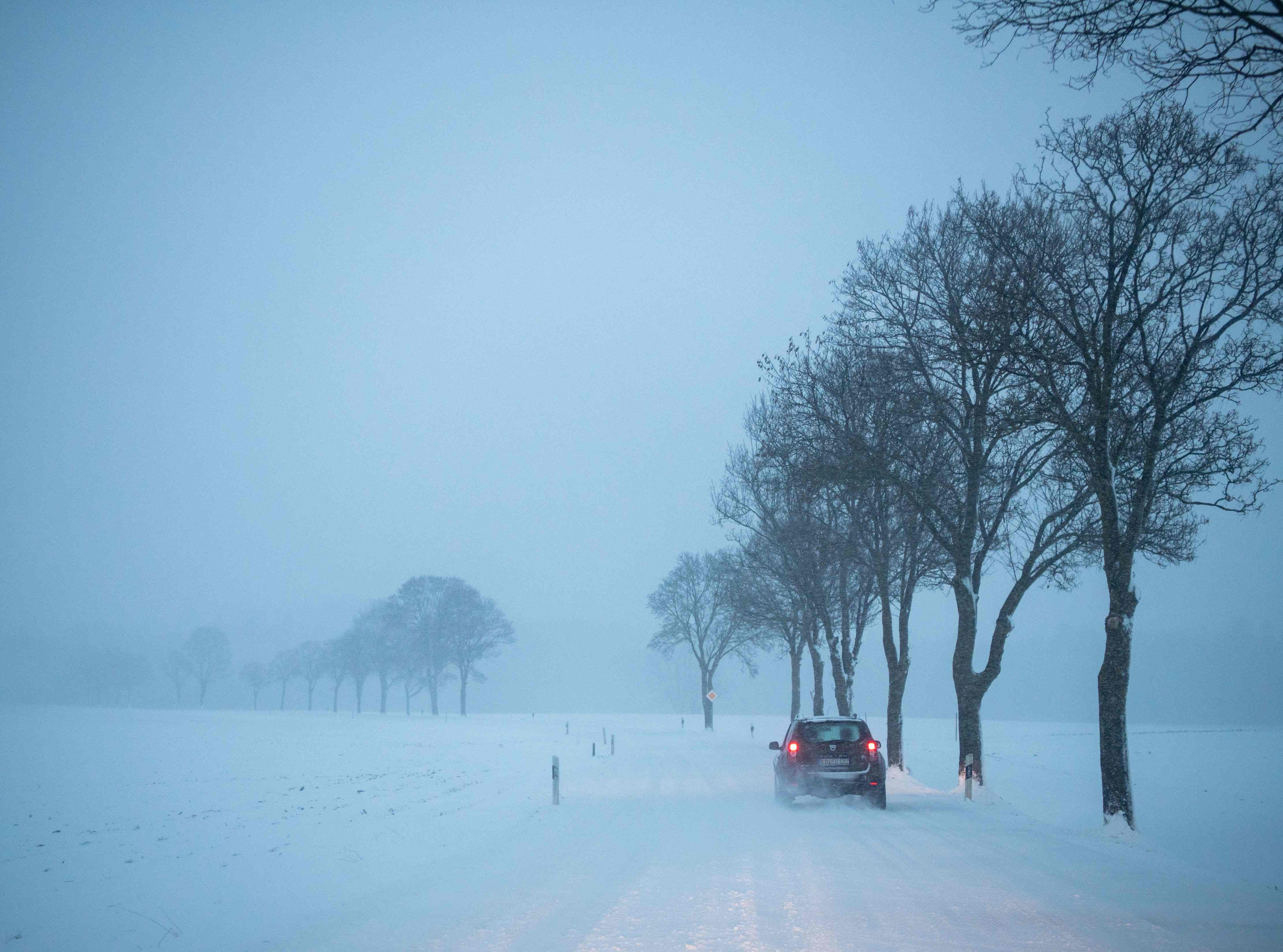 A car drives on a snow-covered road in Hohenlinden, Germany.