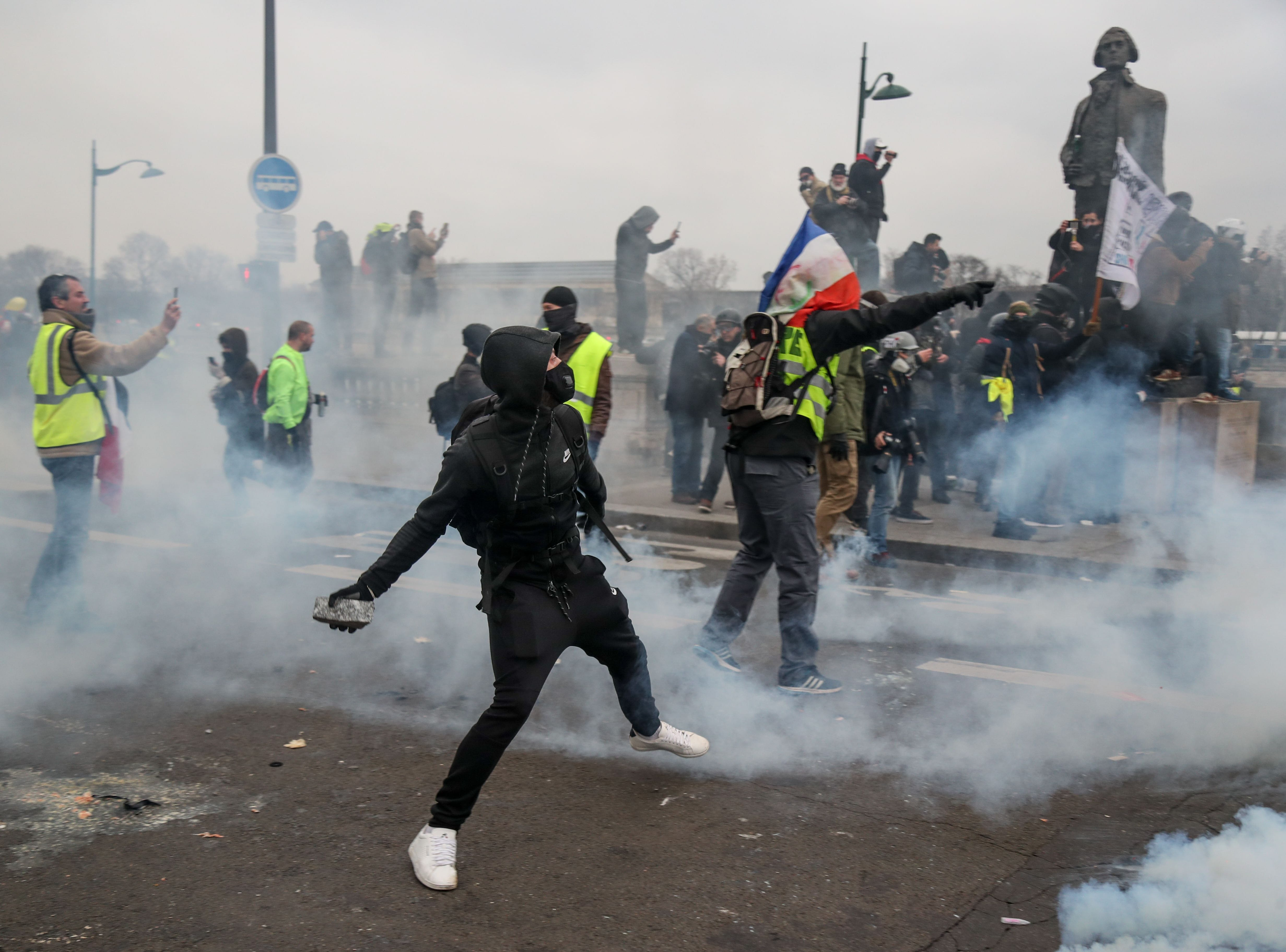 "Yellow vest ""Gilets Jaunes"" anti-government protestors throw stones during clashes with security personnel at a rally in Paris on Jan. 5, 2019."
