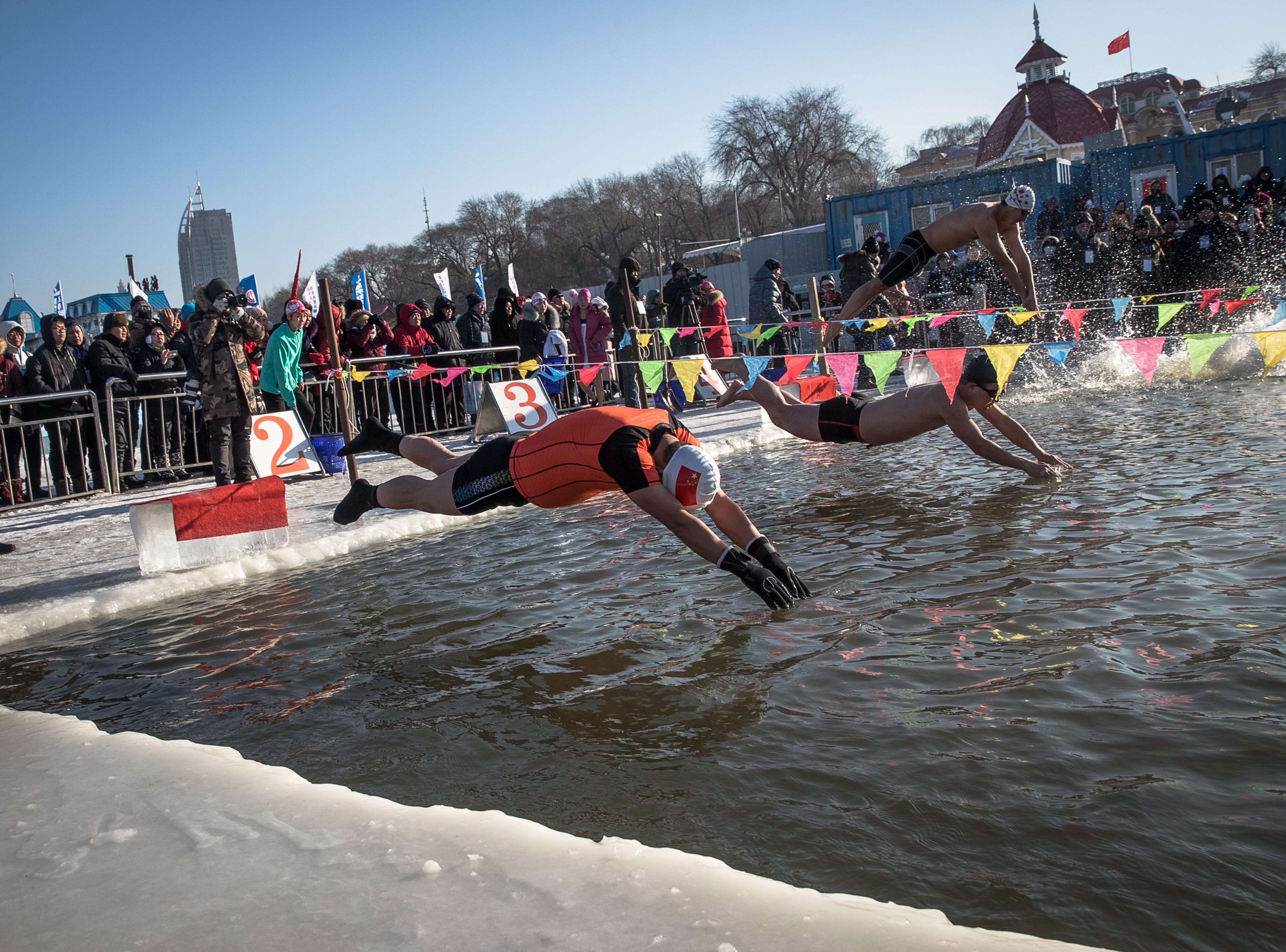 Participants jump into the freezing water of the Songhua River during a winter swimming competition at the annual Harbin International Ice and Snow Sculpture Festival, in Harbin, Heilongjiang province, China on Jan. 5, 2019. Around 600 winter swimmers took part in the competition.