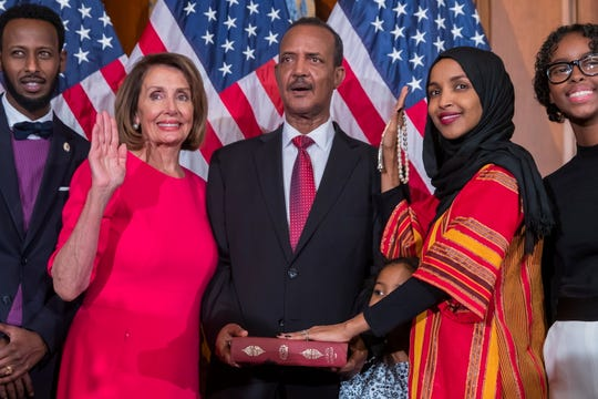 Democratic Representative from Minnesota Ilhan Omar (2-R), uses the Koran of her late grandfather while posing with new Democratic Speaker of the House Nancy Pelosi (2-L), during the first day of the 116th Congress at the US Capitol in Washington, DC