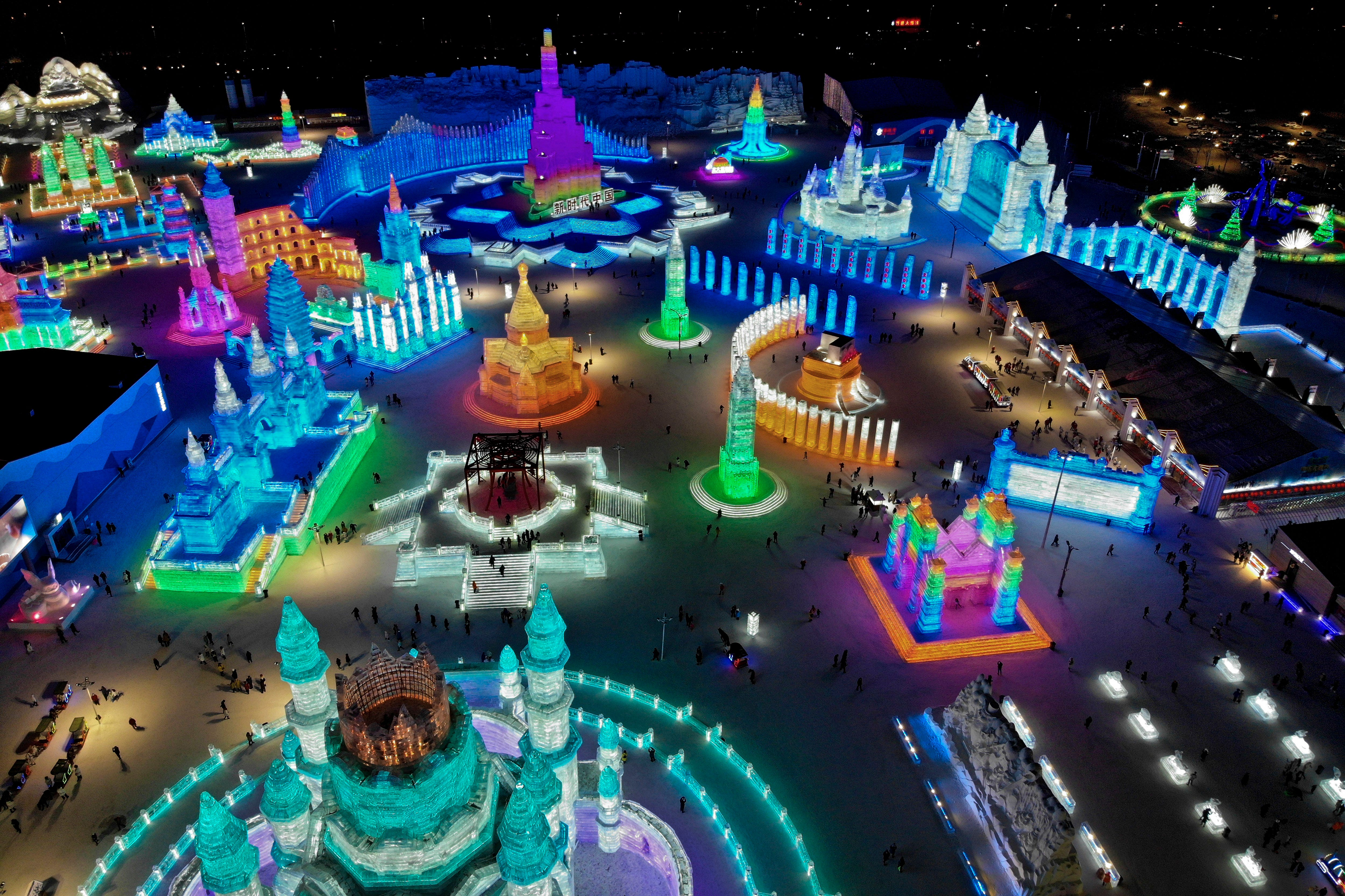 Visitors tour the colorful building structures made from blocks of ice at the Harbin International Ice and Snow festival held in Harbin in northeastern's China's Heilongjiang province, Friday, Jan. 4, 2019. The Harbin International Ice and Snow Festival is known for massive, elaborate and colorfully lit ice sculptures featuring animals, cartoon characters and famous landmarks.