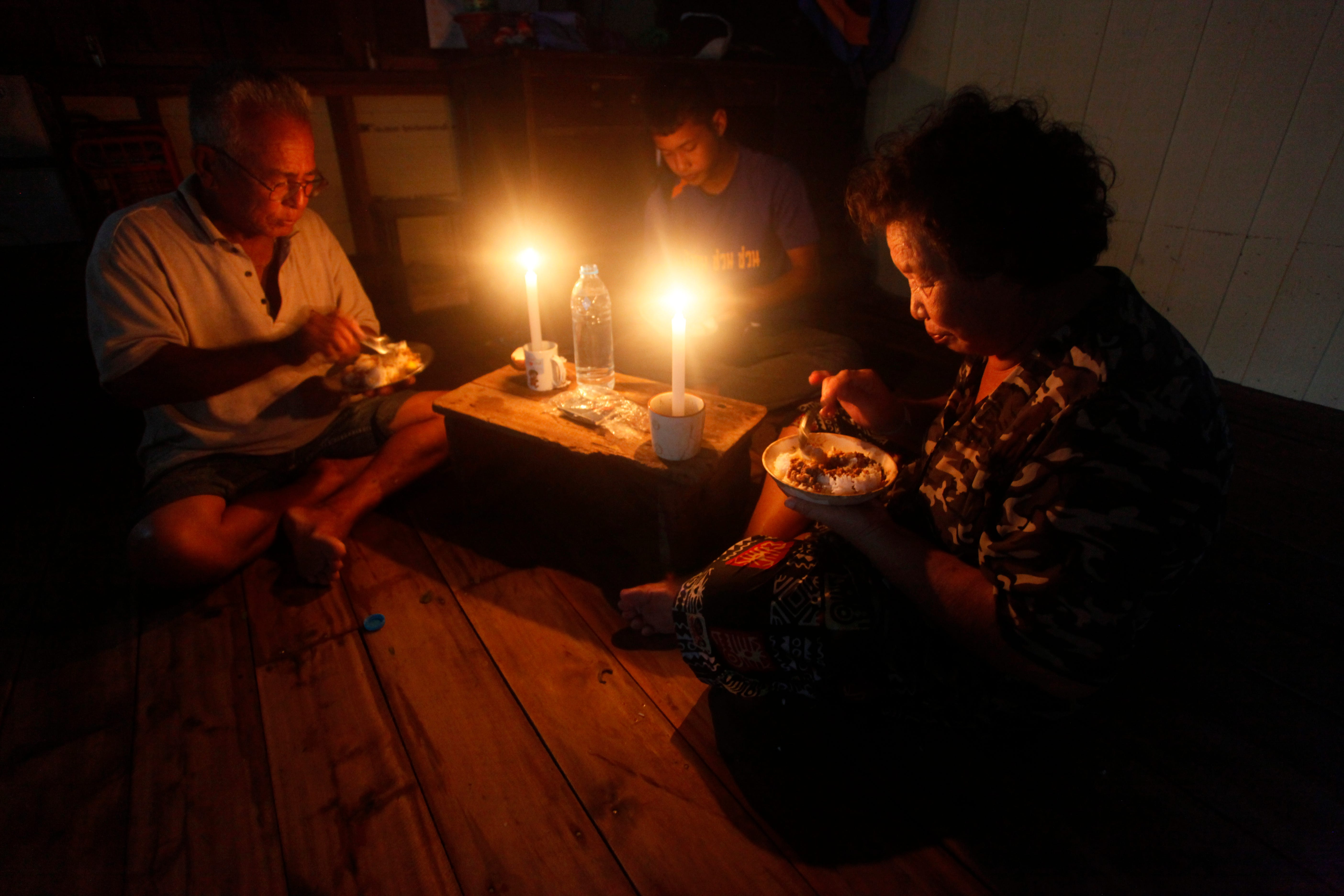 A Thai family eat dinner without electricity in the aftermath of Tropical Storm Pabuk Saturday, Jan. 5, 2019, in Pak Phanang, Nakhon Si Thammarat, province southern Thailand. Ferry services and airports have reopened in southern Thailand after a storm moved west into the Andaman Sea.