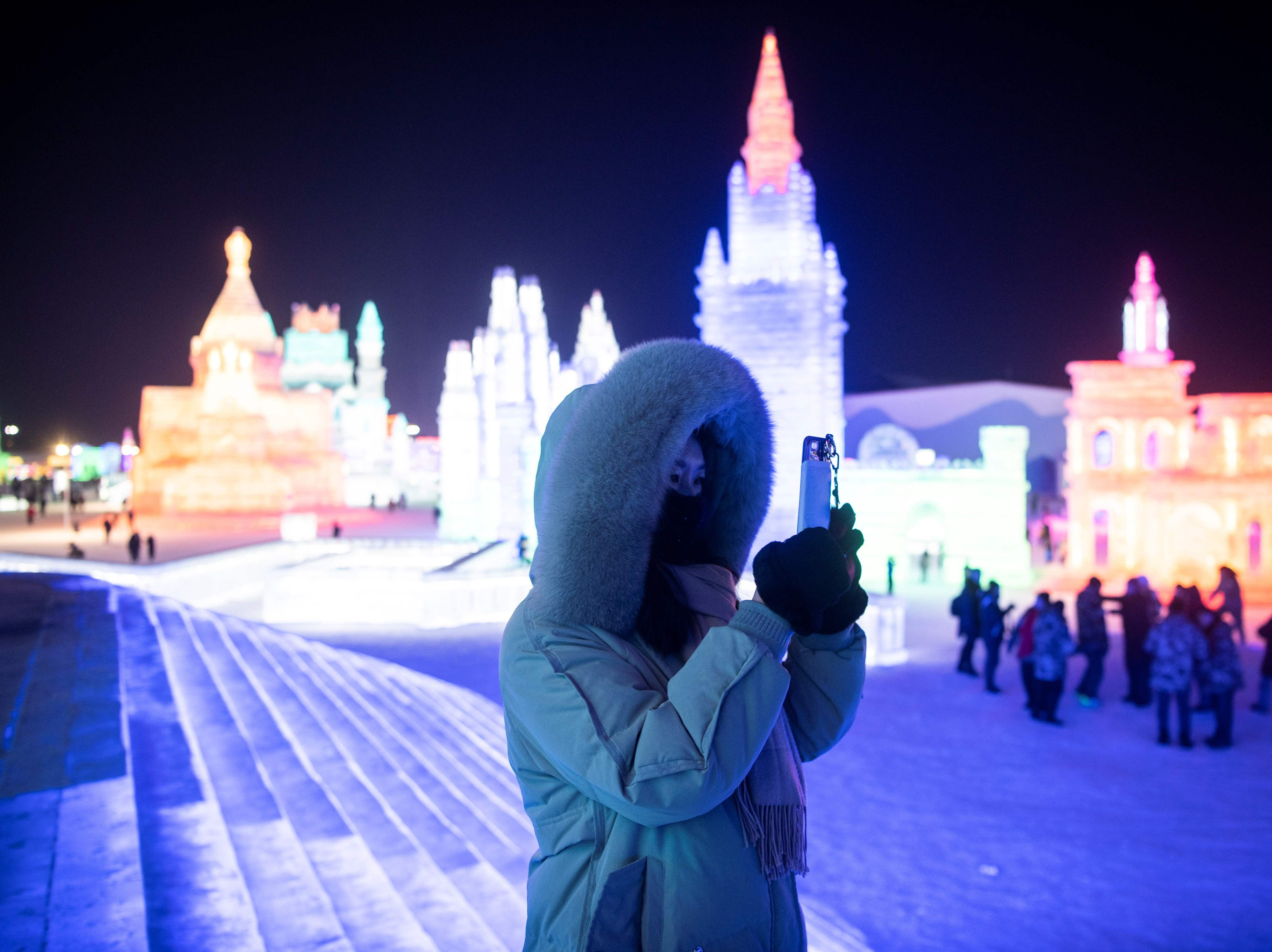 A visitor takes pictures of ice sculptures for the opening day of the annual Harbin Ice and Snow Sculpture Festival in Harbin in China's northeast Heilongjiang province on Jan. 5, 2019.