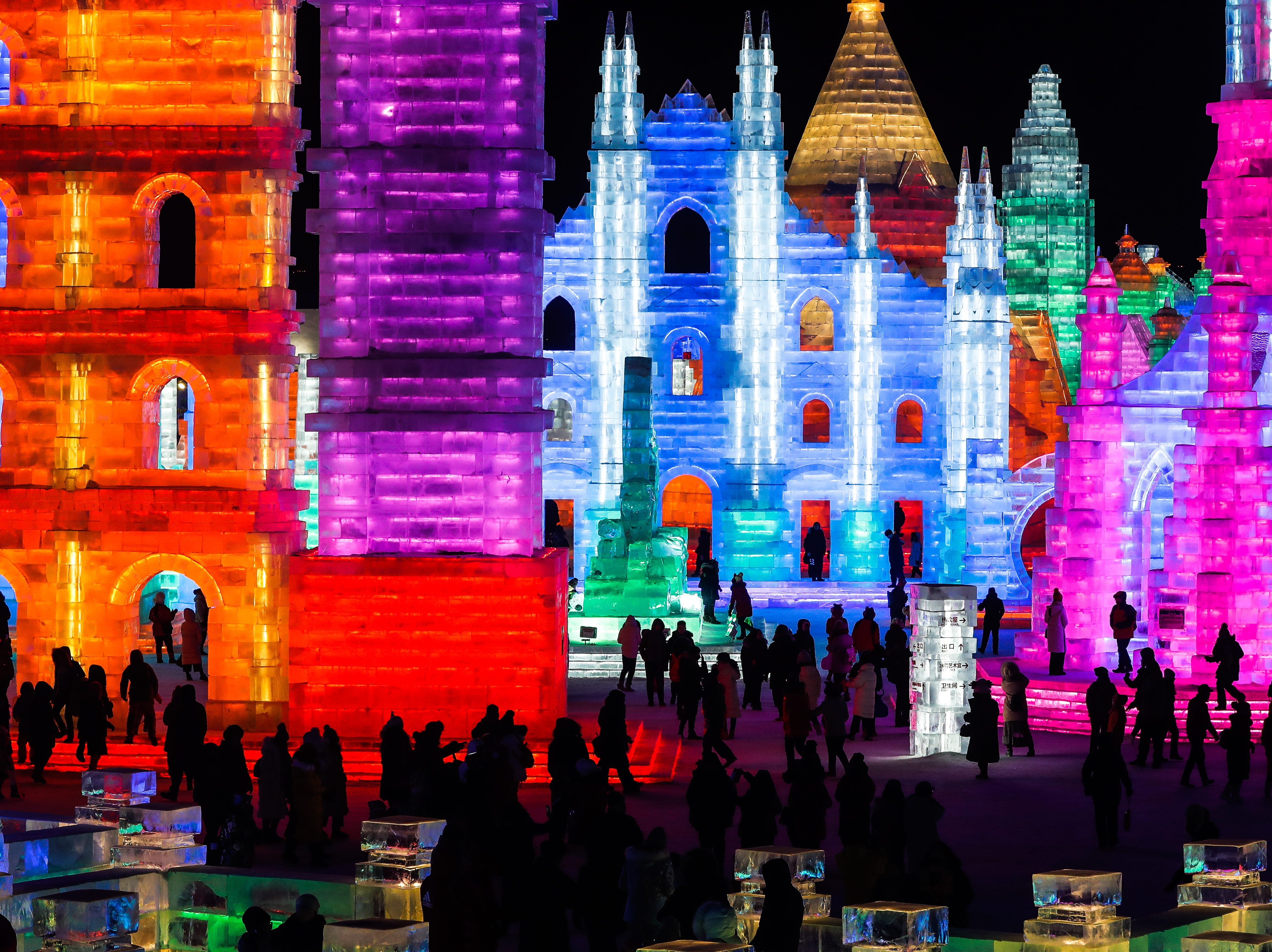 People visit ice sculptures illuminated by colored lights at the Ice and Snow World during the opening ceremony of the annual Harbin International Ice and Snow Sculpture Festival, in Harbin, Heilongjiang province, China on Jan. 5, 2019. Some 120,000 cubic meters of ice and 111,000 cubic meters of snow were used to build the venue of the festival that officially runs from January 5 to February 5.