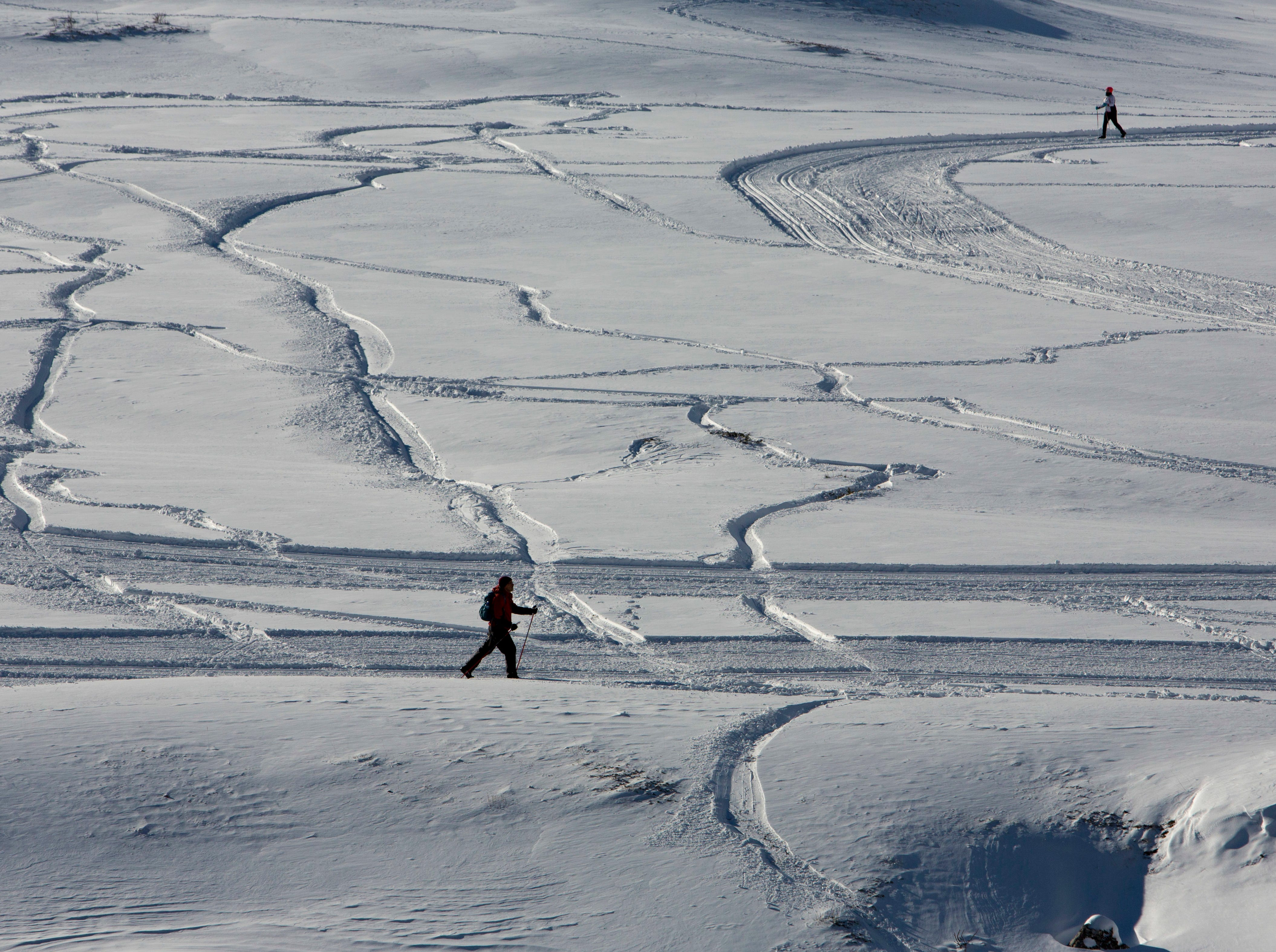 People cross-country ski in Piani di Pezza, near Rocca di Mezzo, Italy, in the Abruzzo region, after a heavy snowstorm, Saturday, Jan. 5, 2019.
