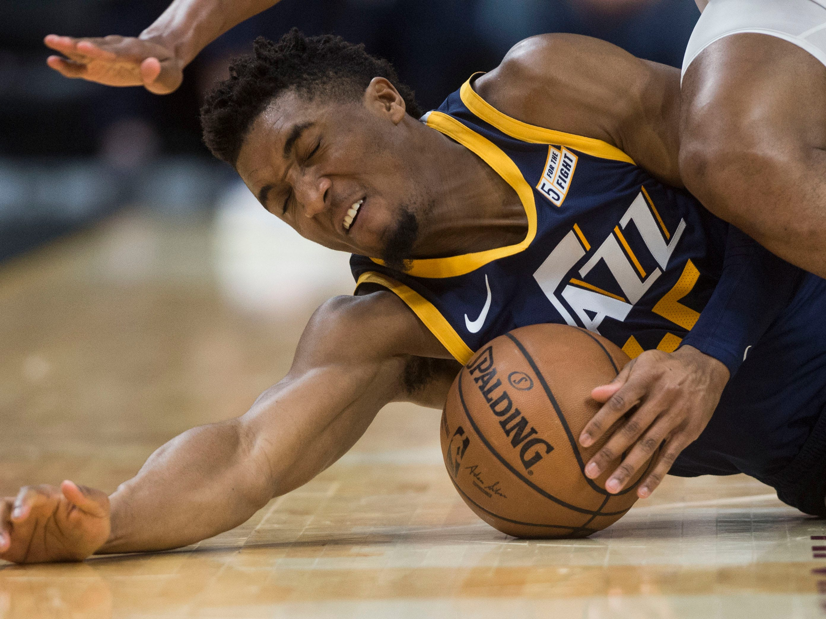 Jan. 4: Jazz guard Donovan Mitchell hits the deck to corral a loose ball during the first half against the Cavaliers at Quicken Loans Arena in Cleveland.