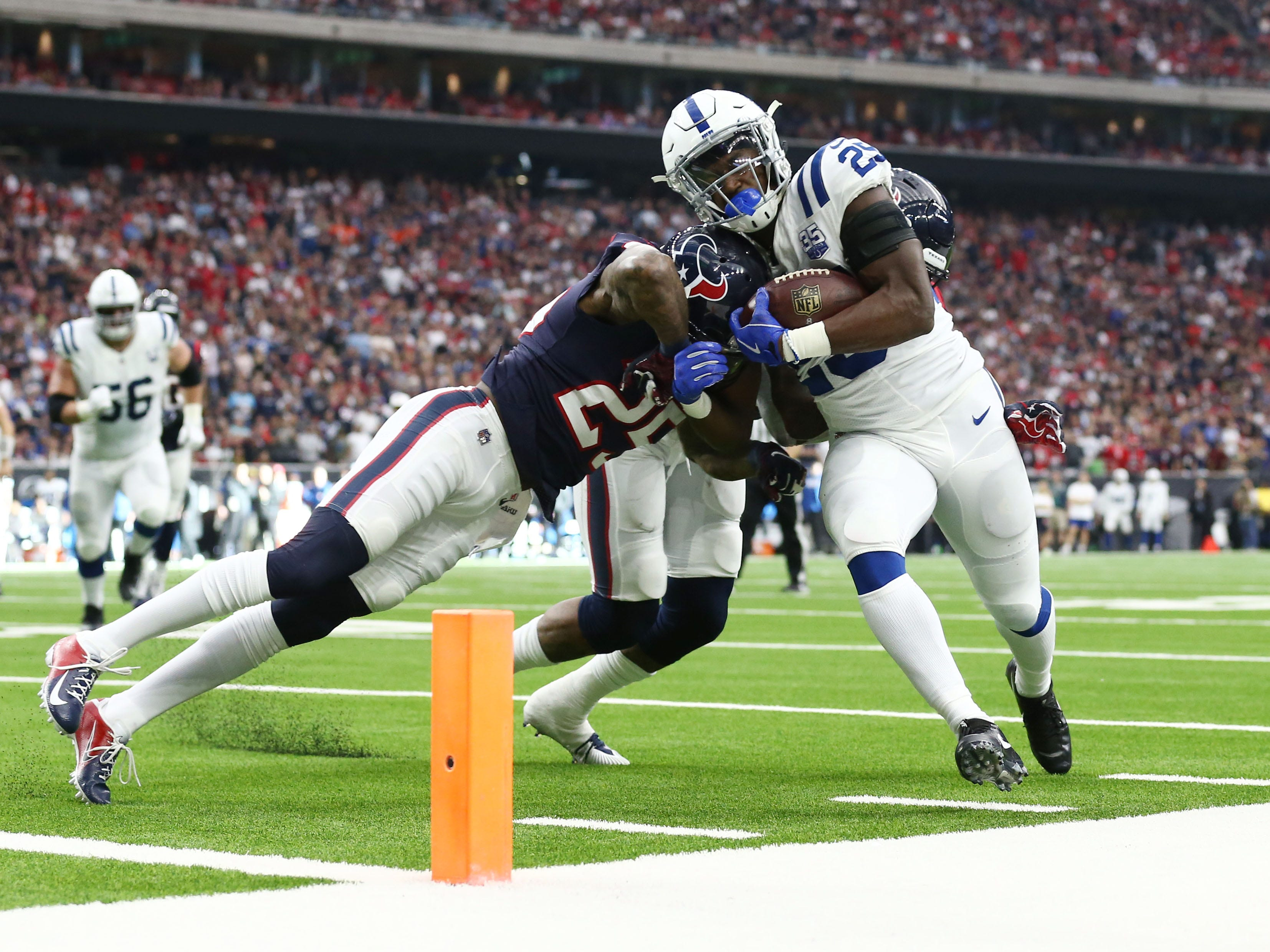 Indianapolis Colts running back Marlon Mack (25) is pushed out of bounds by Houston Texans strong safety Kareem Jackson (25) and inside linebacker Benardrick McKinney (55) in the first quarter in a AFC Wild Card playoff football game at NRG Stadium.