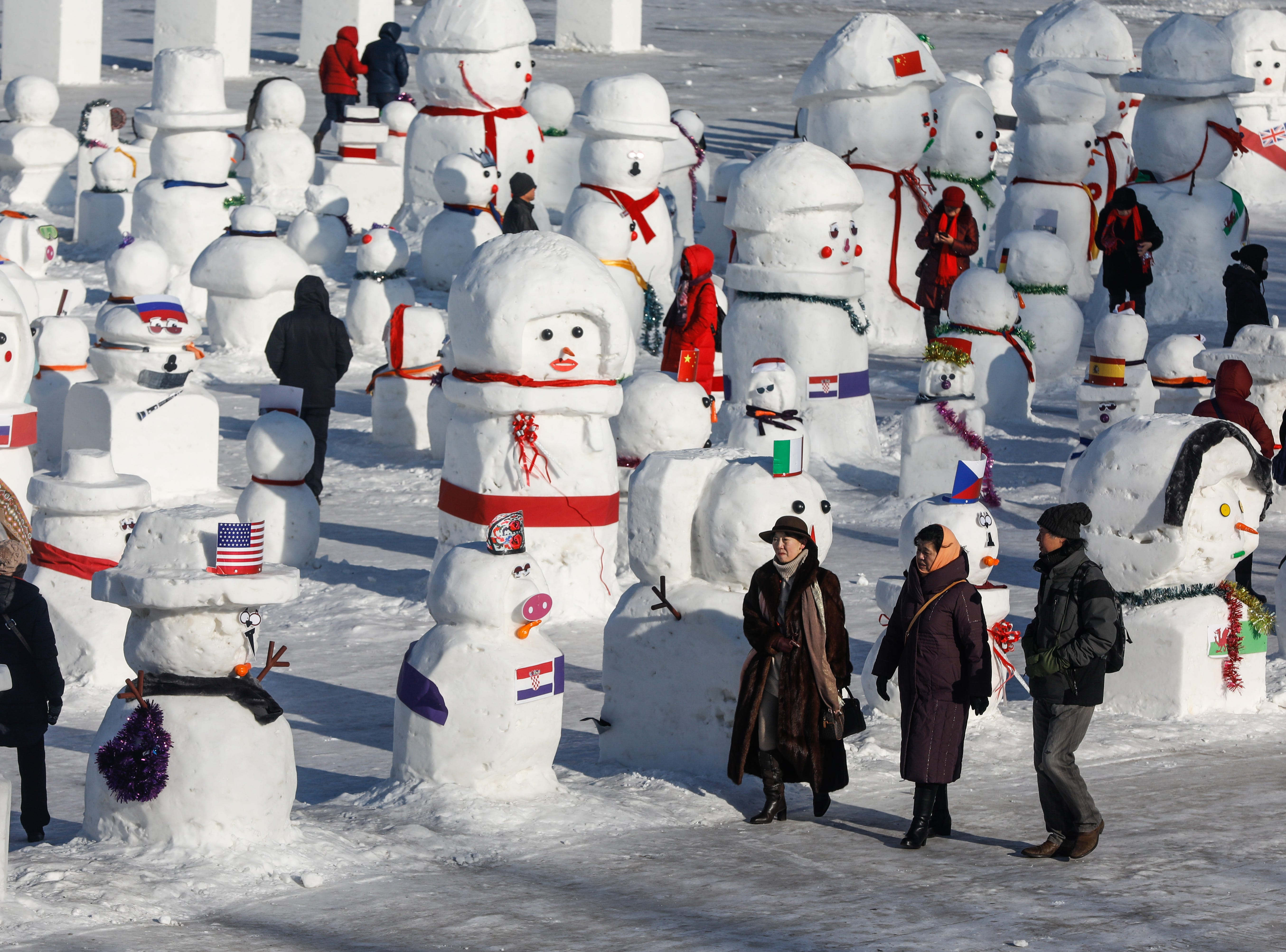 People walk next to snowmen at the Songhua River during the annual International Ice and Snow Festival in Harbin city, China's northern Heilongjiang province on Jan. 5, 2019.