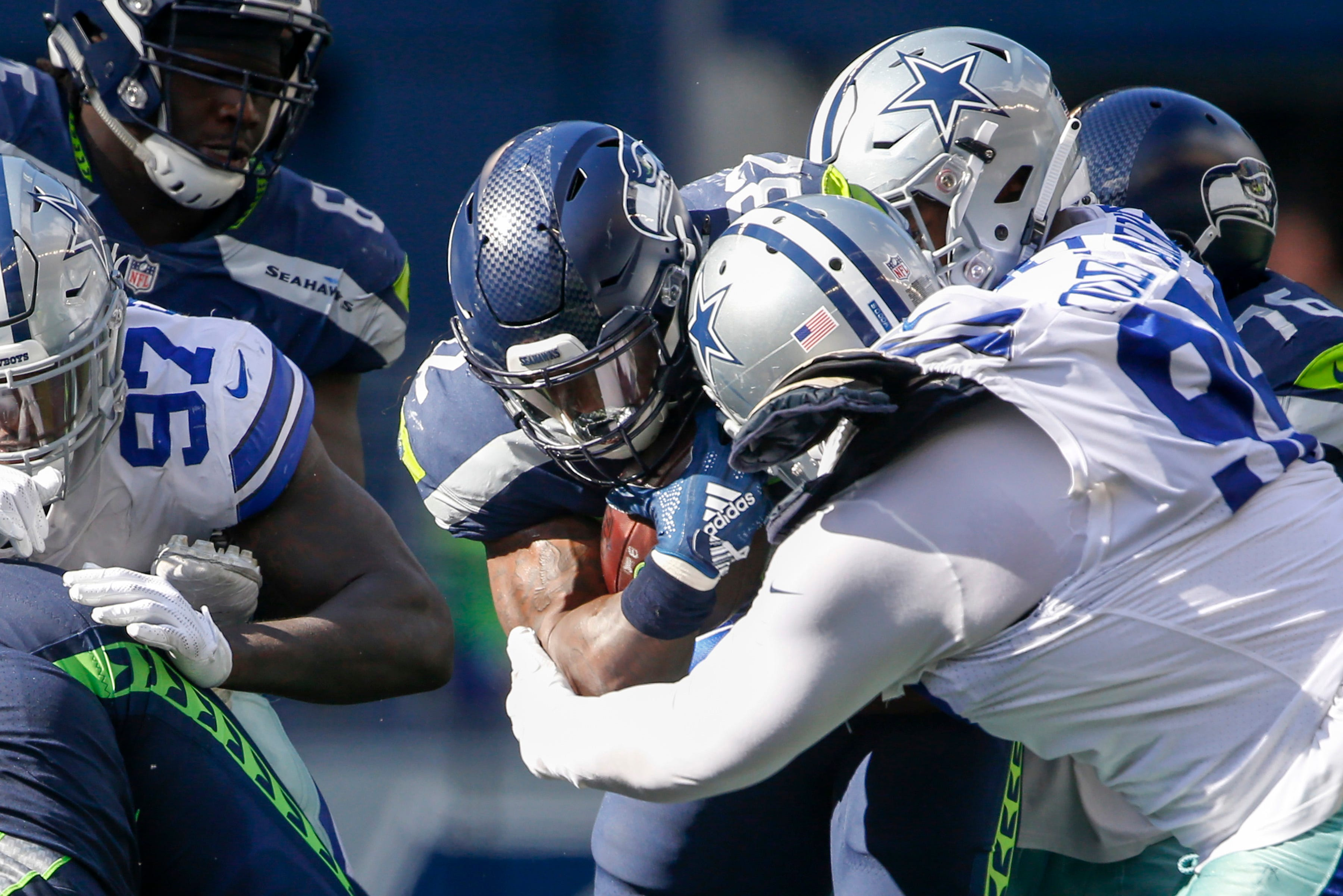 Seattle Seahawks running back Chris Carson (32) is tackled by Dallas Cowboys nose tackle Antwaun Woods (99) during the third quarter at CenturyLink Field.