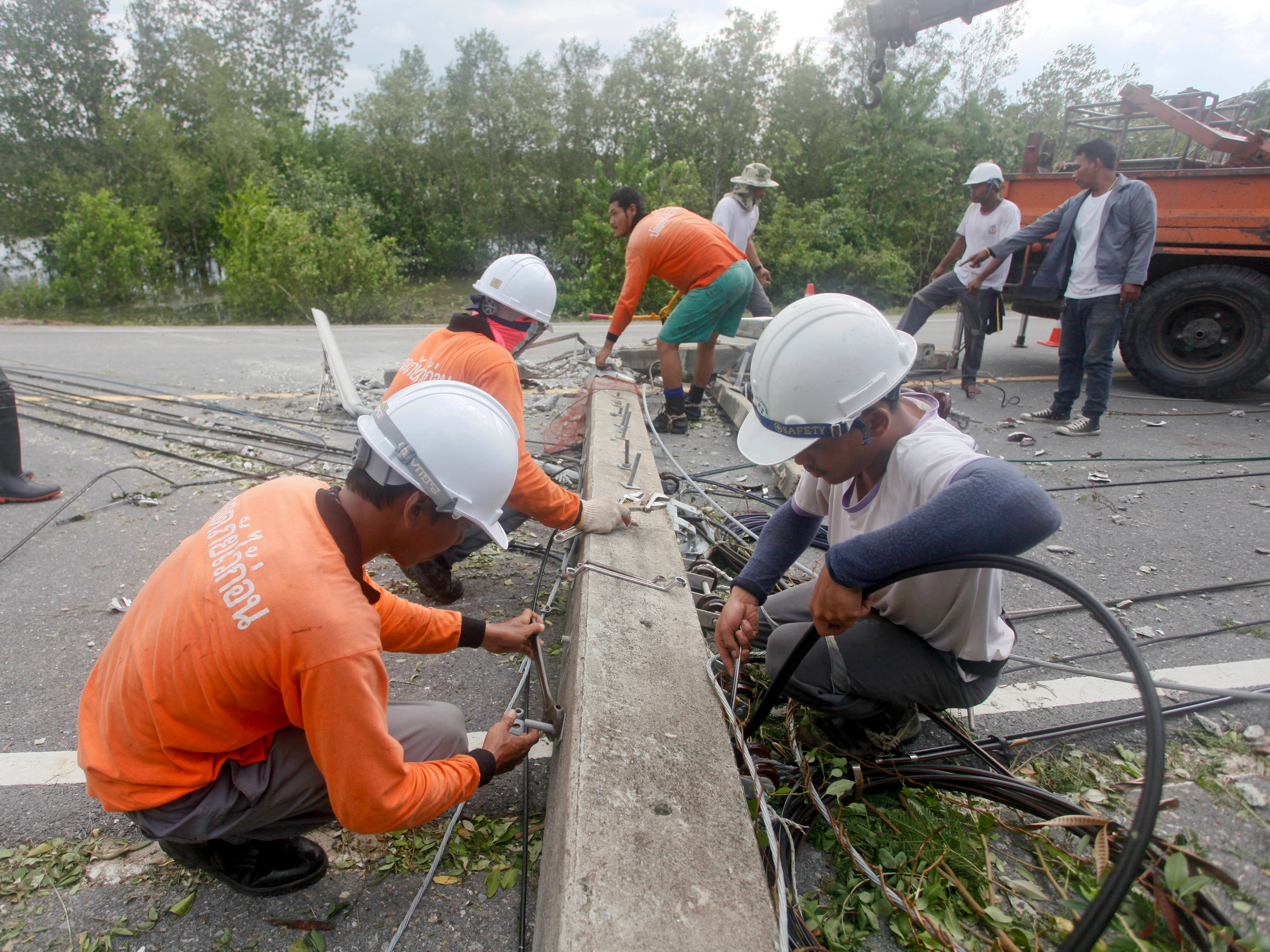 Workers repair toppled power lines in the aftermath of Tropical Storm Pabuk Saturday, Jan. 5, 2019, in Pak Phanang, in the southern province of Nakhon Si Thammarat, southern Thailand. The storm damaged houses, knocked down power lines and triggered flash floods in several east coast provinces.
