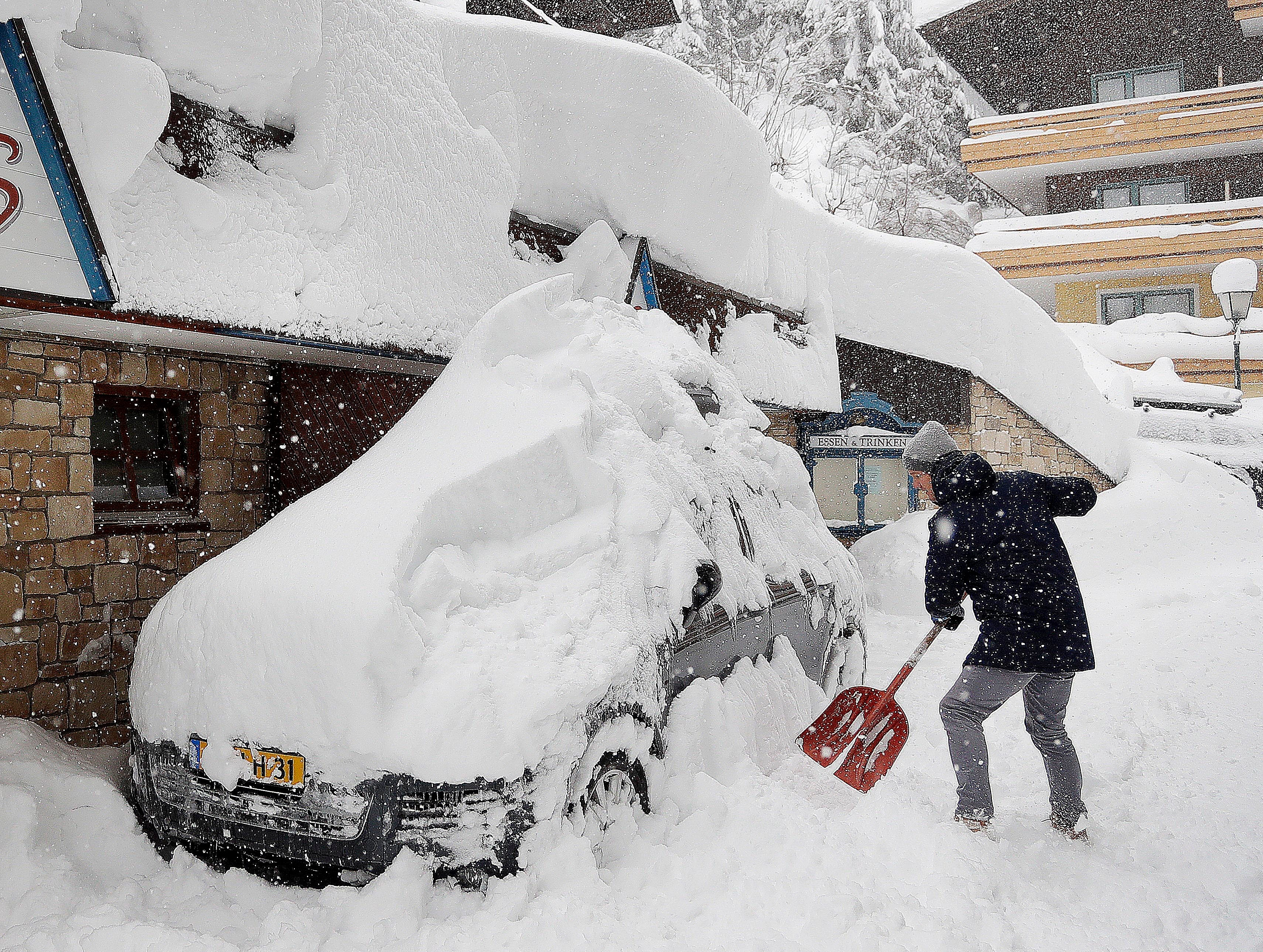 A ski tourist removes snow from a car after heavy snow falls in Filzmoos, Austria, Saturday, Jan. 5, 2019.