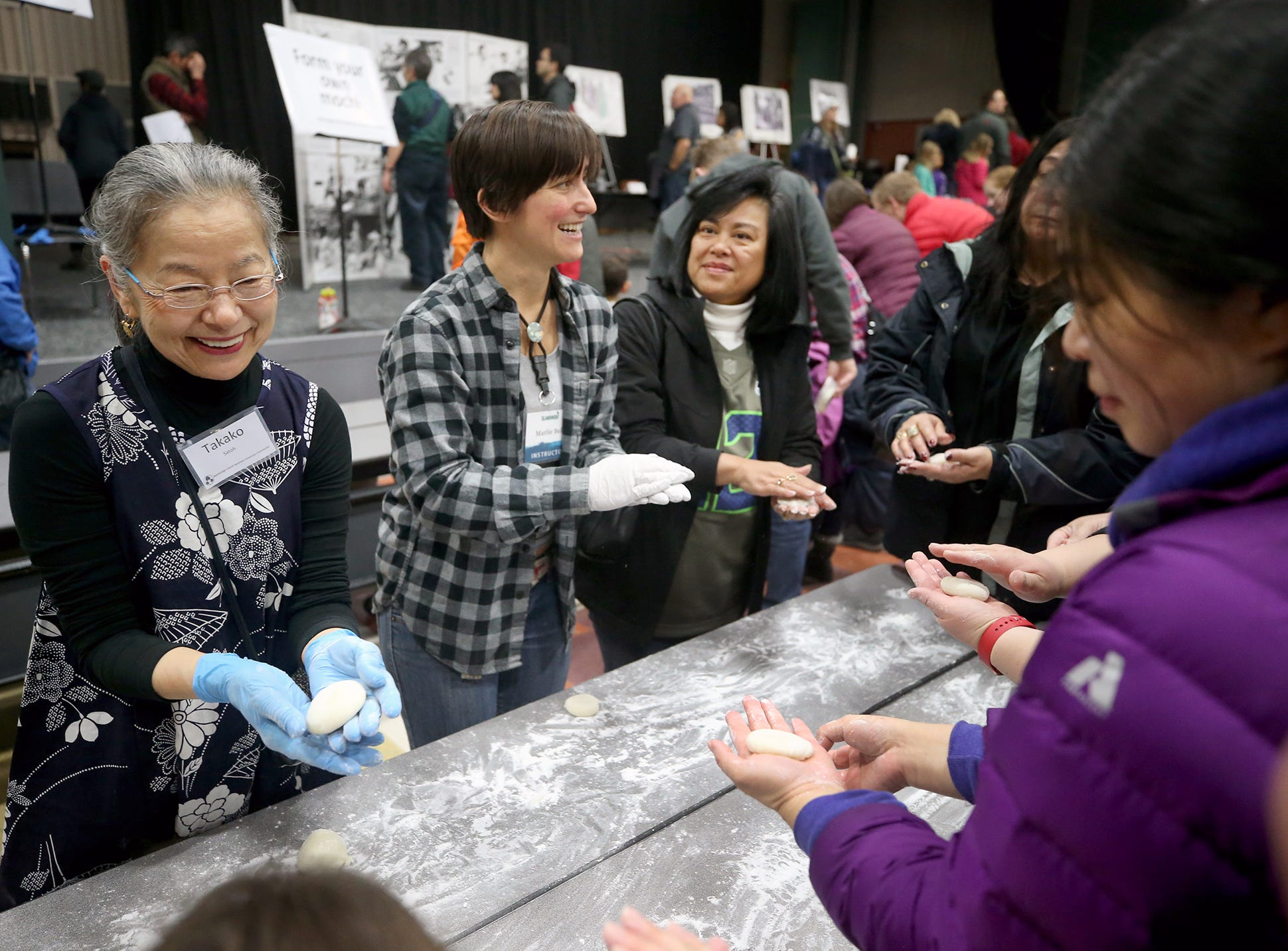 The 30th anniversary of Bainbridge Island's Japanese-American Mochi Tsuki celebration was held at an new location at the Woodward Middle School on Saturday, January, 5, 2019. Mochi Tsuki is a traditional Japanese New Year's tradition of steaming rice and pounding it into a rice cake. Takako Satoh of Bainbridge Island shows how to make a rice mochi ball to visitors.