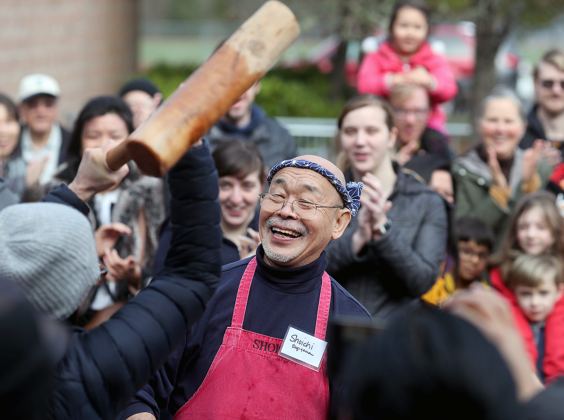 The 30th anniversary of Bainbridge Island's Japanese-American Mochi Tsuki celebration was held at an new location at the Woodward Middle School on Saturday, January, 5, 2019. Mochi Tsuki is a traditional Japanese New Year's tradition of steaming rice and pounding it into a rice cake. Master mochi maker Shoichi Sugiyama, center, makes jokes as a volunteer lifts the heavy mallet to pound rice.