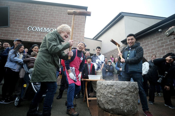 The 30th anniversary of Bainbridge Island's Japanese-American Mochi Tsuki celebration was held at an new location at the Woodward Middle School on Saturday, January, 5, 2019. Mochi Tsuki is a traditional Japanese New Year's tradition of steaming rice and pounding into a rice cake. Sharen Iversen, left, of Poulsbo is embarrassed after she missed pounding the sweet rice in the stone bowl with her mallet as master mochi maker Shoichi Sugiyama, center, reacts. Near them is Collin Tasaka of Mill Creek.