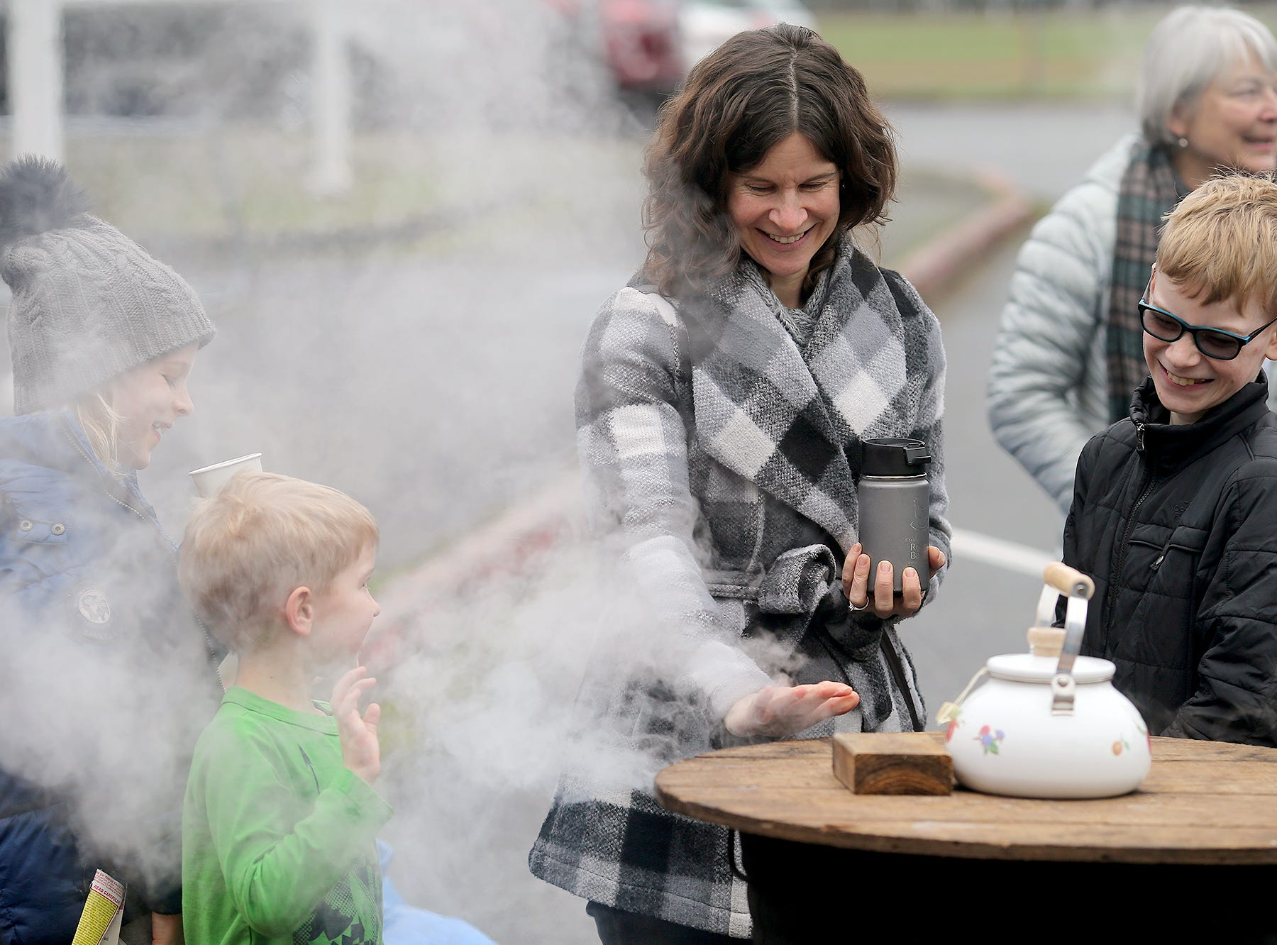 The 30th anniversary of Bainbridge Island's Japanese-American Mochi Tsuki celebration was held at an new location at the Woodward Middle School on Saturday, January, 5, 2019. Mochi Tsuki is a traditional Japanese New Year's tradition of steaming rice and pounding into a rice. Nicole Bavo, center, of Bainbridge Island warms her hand on the wood-fired water heater for the rice cooker with her sons Ethan Meidell, 8, left, Luke, 5, and Adrian, 10.