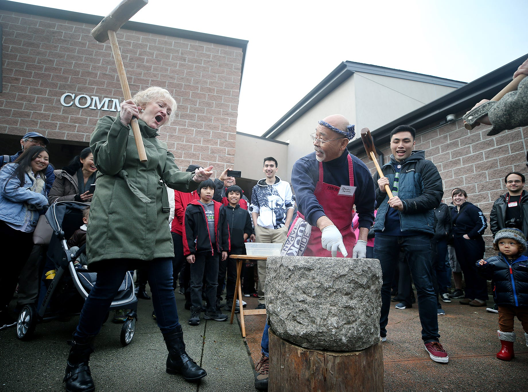 The 30th anniversary of Bainbridge Island's Japanese-American Mochi Tsuki celebration was held at an new location at the Woodward Middle School on Saturday, January, 5, 2019. Mochi Tsuki is a traditional Japanese New Year's tradition of steaming rice and pounding it into a rice cake. Sharen Iversen, left, of Poulsbo is embarrassed after she missed pounding the sweet rice in the stone bowl with her mallet. Master mochi maker Shoichi Sugiyama, center, points to the place to pound. Behind them is Collin Tasaka of Mill Creek.
