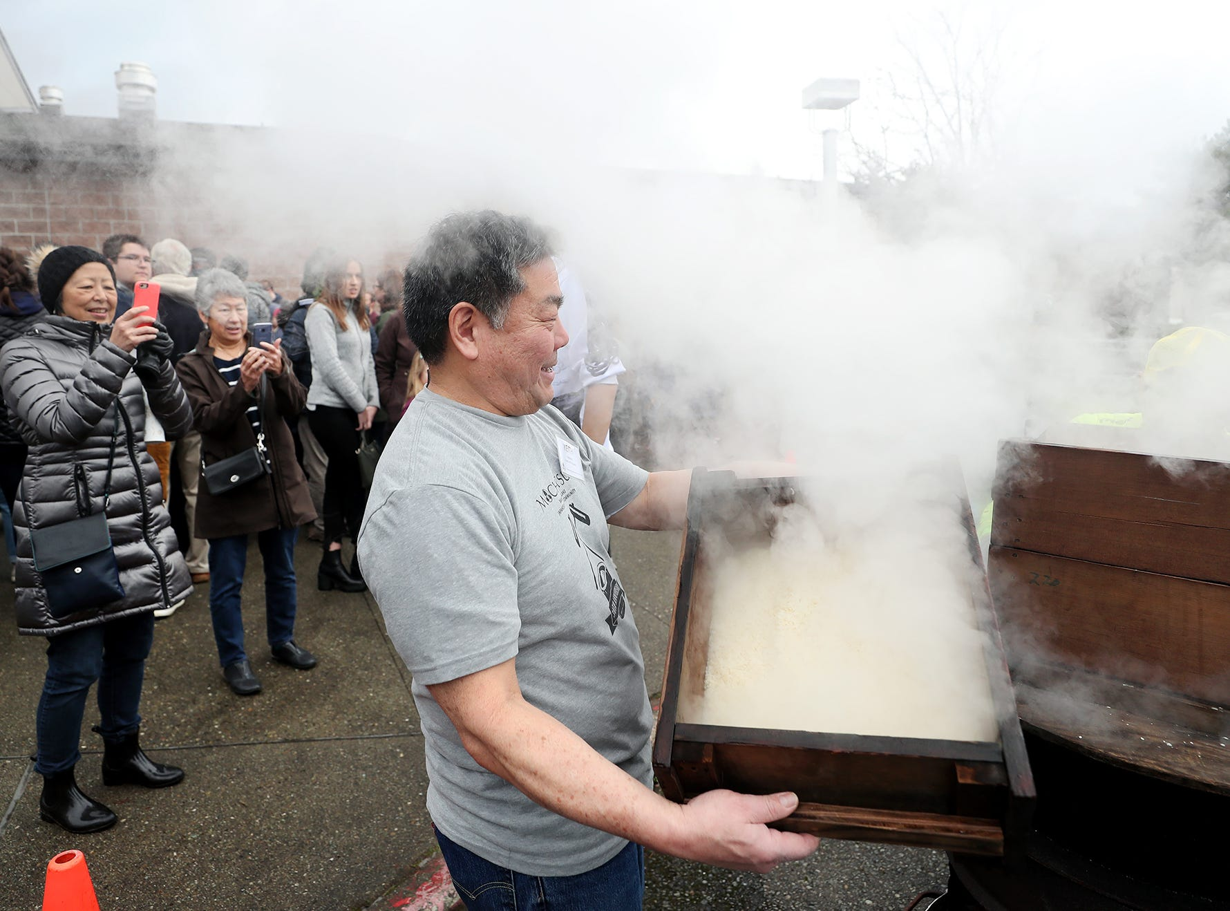 The 30th anniversary of Bainbridge Island's Japanese-American Mochi Tsuki celebration was held at an new location at the Woodward Middle School on Saturday, January, 5, 2019. Mochi Tsuki is a traditional Japanese New Year's tradition of steaming rice and pounding into a rice. Keith Uyekawa takes away cooked steam sweet rice from the wood cooker.