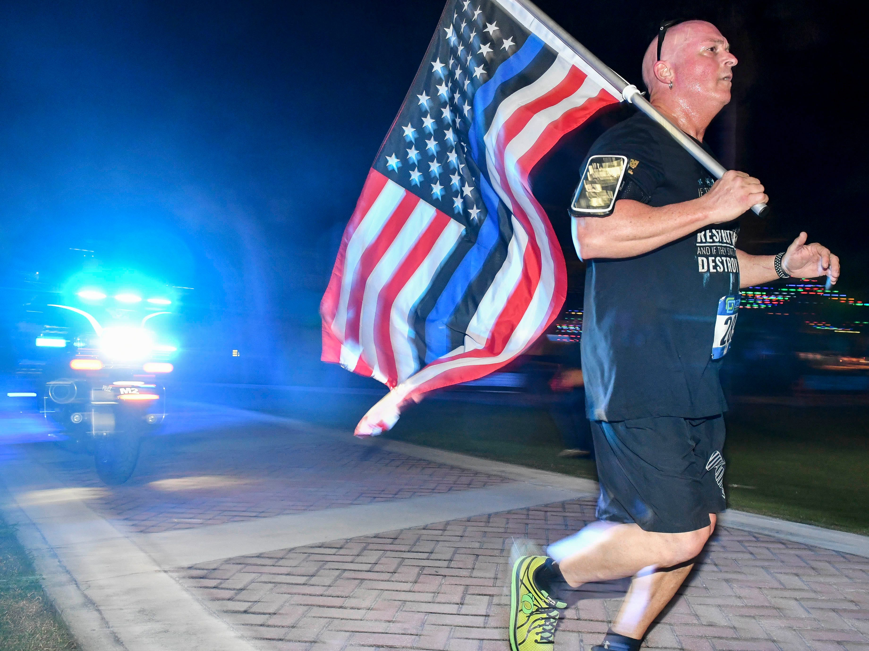 James Dean carries a flag as he runs in the inaugural Game On Run for Responders 5K Run/Walk run through the streets of Cocoa Village Saturday.  Proceeds from the event benefit Survive First, a nonprofit that aids first responders and their families with mental health issues.