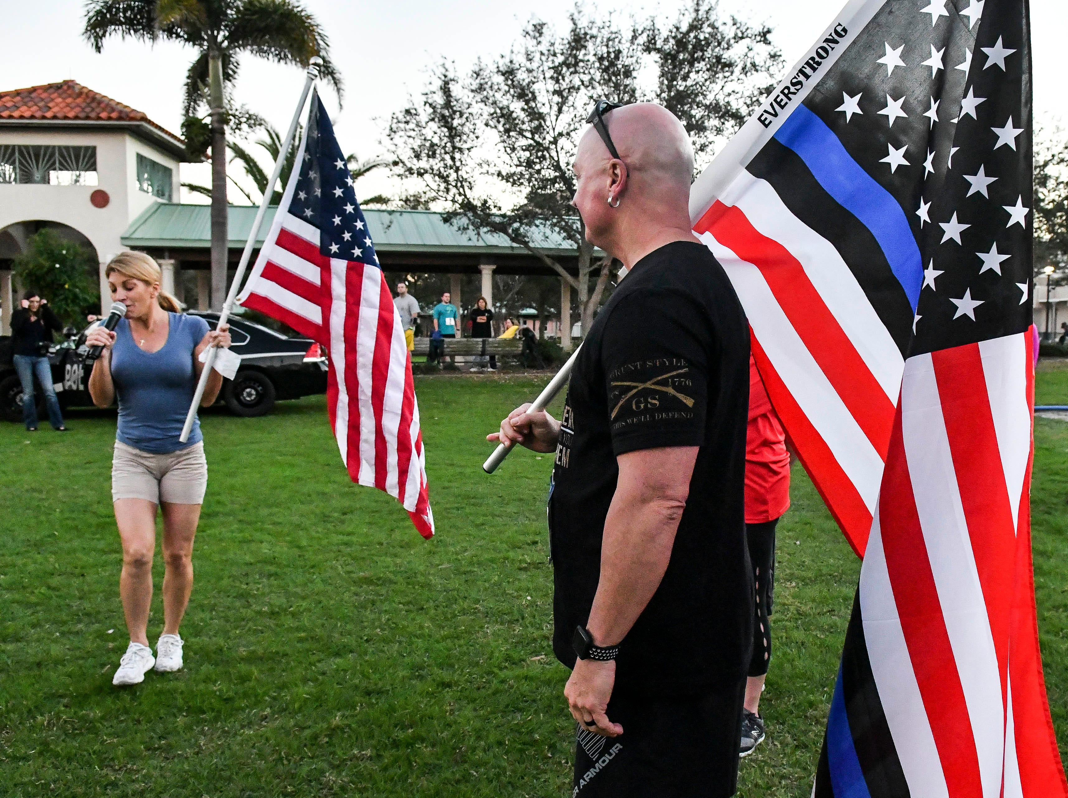 Donna Bollinger and James Dean hold flags as Donna sings the National Anthem prior to the start of the inaugural Game On Run for Responders 5K Run/Walk in Cocoa Village.  Proceeds from the event benefit Survive First, a nonprofit that aids first responders and their families with mental health issues.