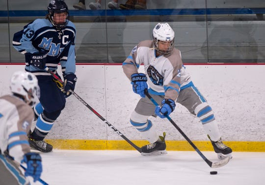 South Burlington's Gabe Frigo, right, collects the puck along the boards during Saturday night's boys hockey game at Cairns Arena in South Burlington on Jan. 5, 2019.