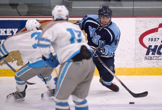 Mount Mansfield's Macauley Bernier, right, cuts back along the boards during Saturday night's boys hockey game at Cairns Arena in South Burlington on Jan. 5, 2019.
