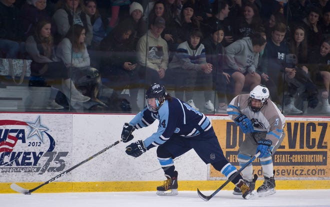 Mount Mansfield's Patrick Burke, left, chases the puck up the boards against South Burlington during Saturday night's boys hockey game at Cairns Arena in South Burlington on Jan. 5, 2019.