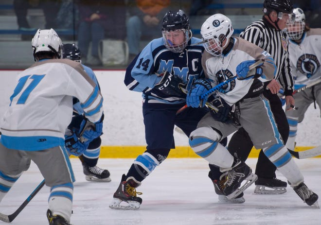 Mount Mansfield's Patrick Burke, center, stands up South Burlington's Isaac Toupin after a faceoff during Saturday night's boys hockey game at Cairns Arena in South Burlington on Jan. 5, 2019.