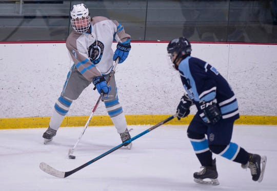 South Burlington's Hunter Fay, left, looks to pass the puck against Mount Mansfield during Saturday night's boys hockey game at Cairns Arena in South Burlington on Jan. 5, 2019.