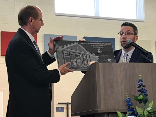 School board President Steve Mullins, left, accepts a commemorative plaque from Charlie Jahnigen, architect for SHP Leading Design.