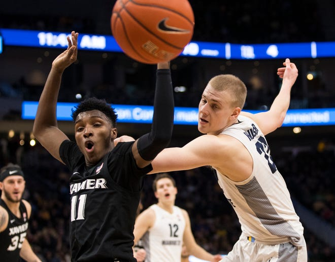 Xavier Musketeers guard Keonte Kennedy (11) and forward Joey Hauser (22) chase the loose ball during the first half at Fiserv Forum.