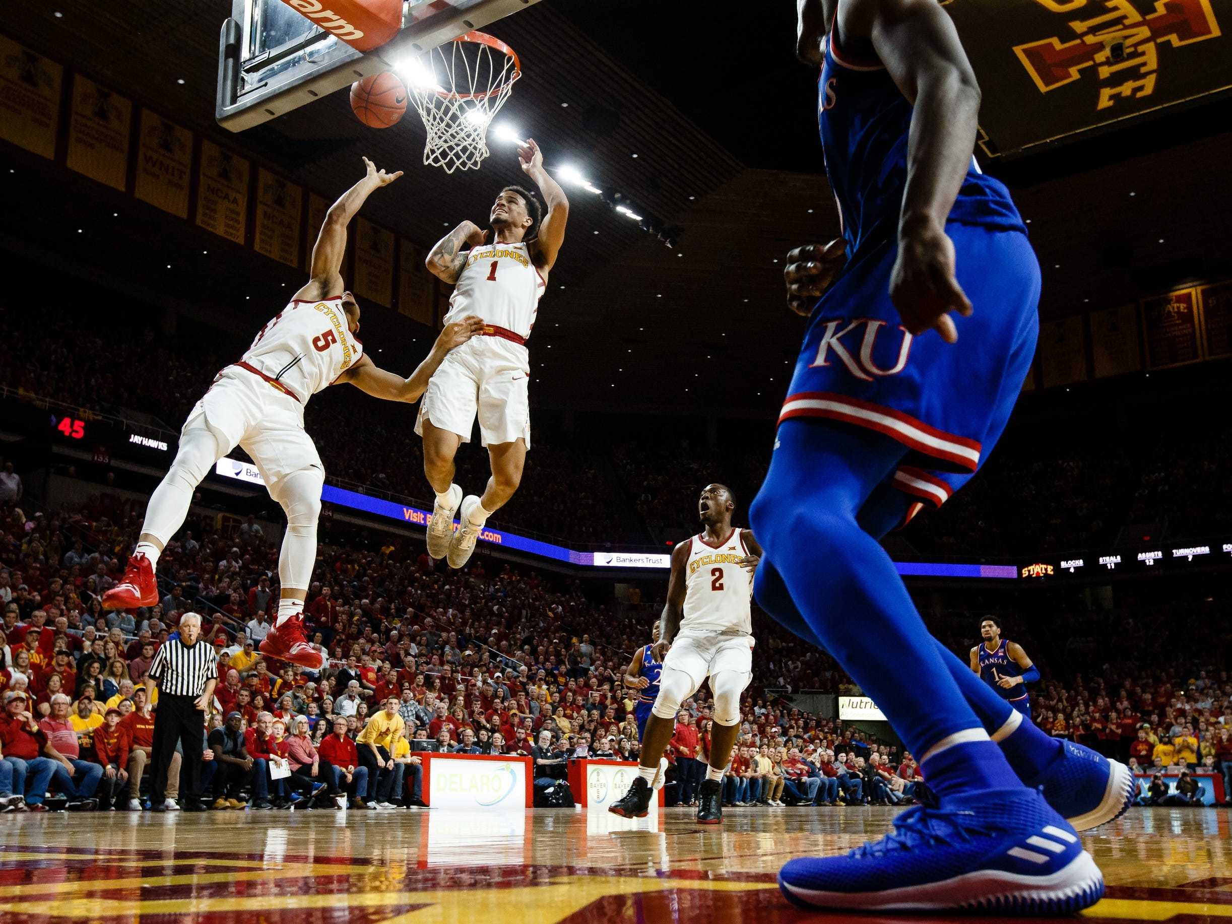 Iowa State's Lindell Wigginton (5) and Iowa State's Nick Weiler-Babb (1) make sure Wiggington's layup goes in during the second half of their basketball game on Saturday, Jan. 5, 2019, in Ames. Iowa State would go on to beat Kansas 77-60.