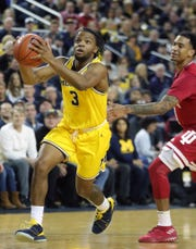 Michigan guard Zavier Simpson drives against Indiana guard Devonte Green during the first half on Sunday, January 6, 2019 at Crisler Center in Ann Arbor.