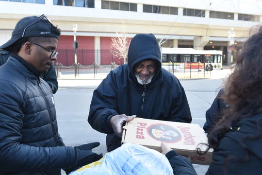 Homeless men receive winter gloves, a jacket, and pizza during the 4th Annual 1Humanity Pizza Drive in Detroit on Sunday, January 6, 2019. 