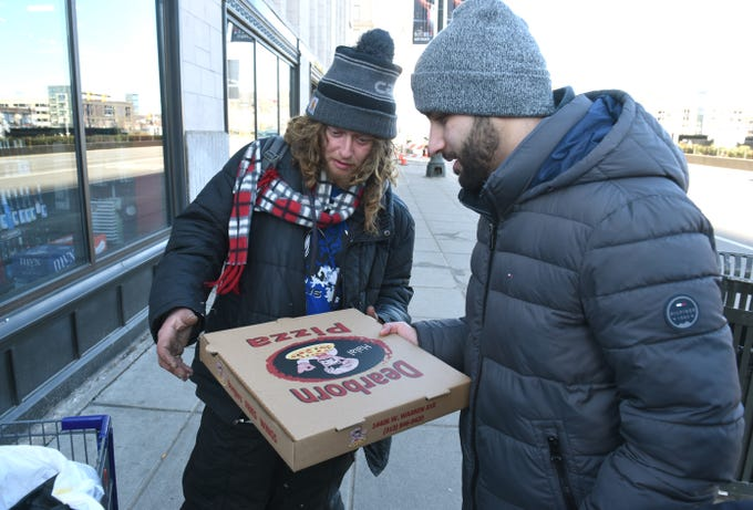 Ali Bazzi (right), founder, 1Humanity Pizza Drive,  speaks with Shawn Pastula and gives him a pizza during the 4th Annual 1Humanity Pizza Drive in Detroit on Sunday, January 6, 2019.