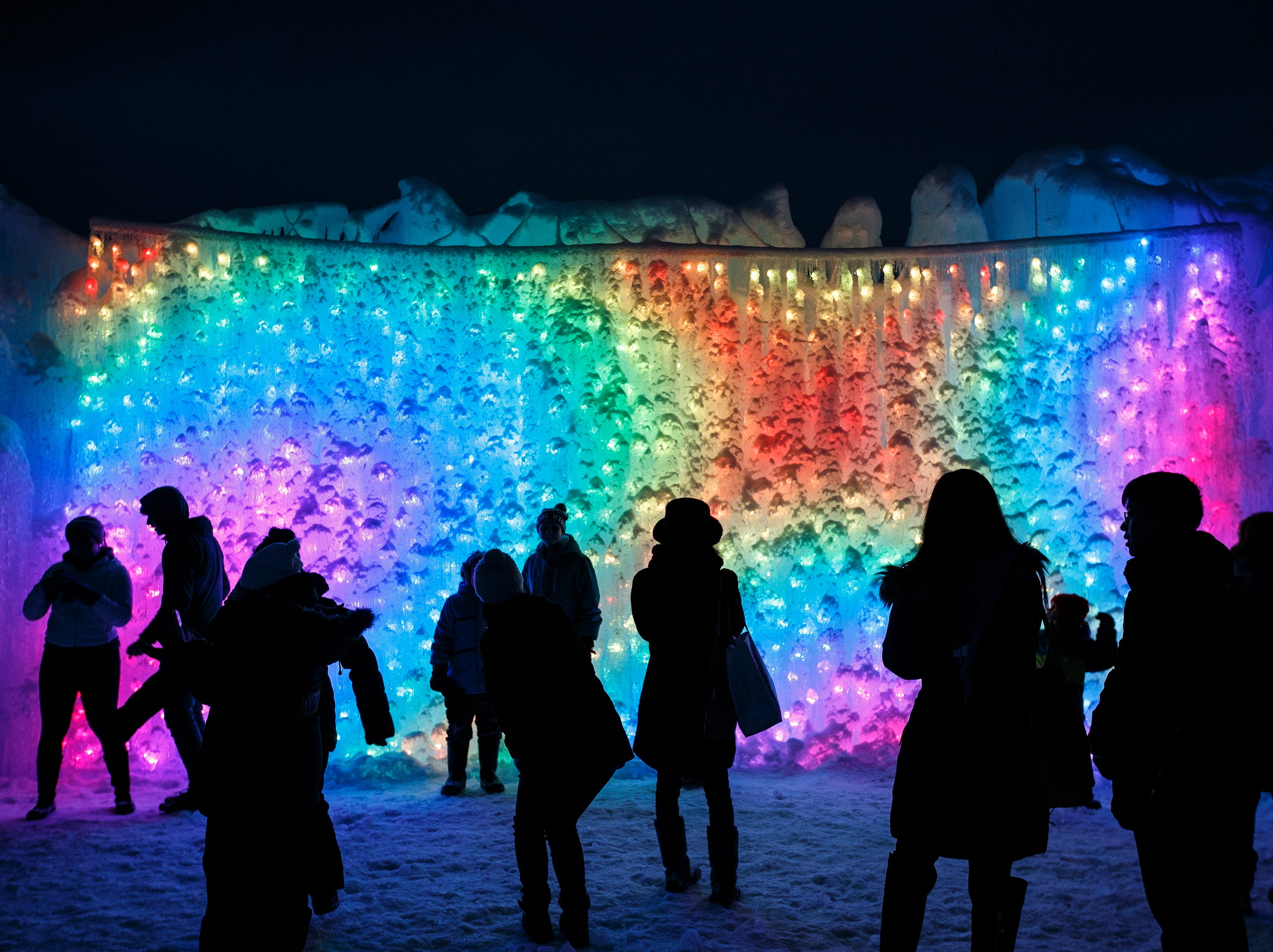 Visitors gather around an ice wall inside an Ice Castle in Edmonton Alberta, on Friday, Jan. 4, 2019. The attraction was built by Ice Castles, LLC and features ice-carved tunnels, fountains, slides, frozen thrones, and cascading towers of ice embedded with color-changing LED lights that twinkle to music at night.
