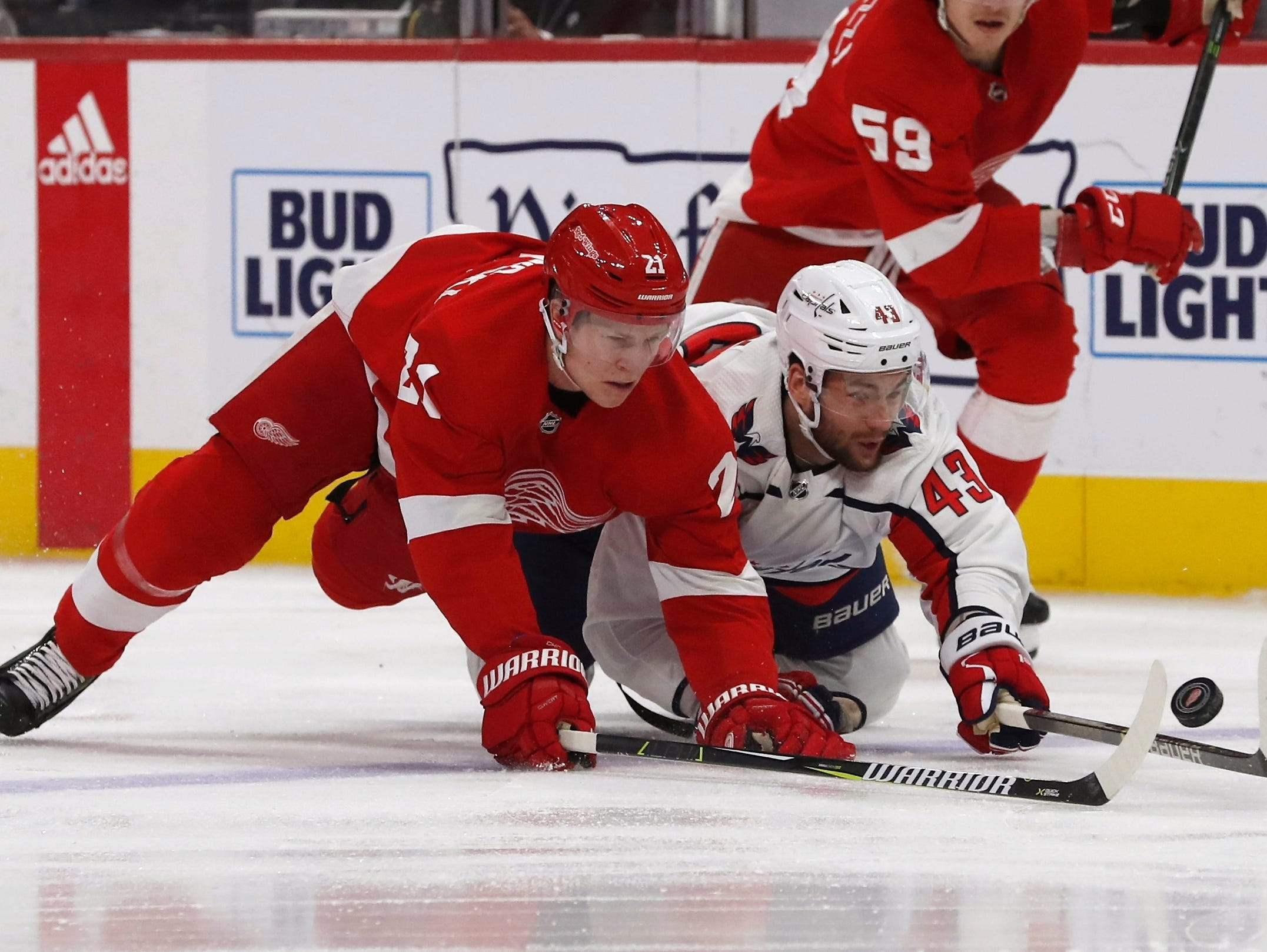 Detroit Red Wings defenseman Dennis Cholowski (21) and Washington Capitals right wing Tom Wilson (43) reach for the puck during the first period.