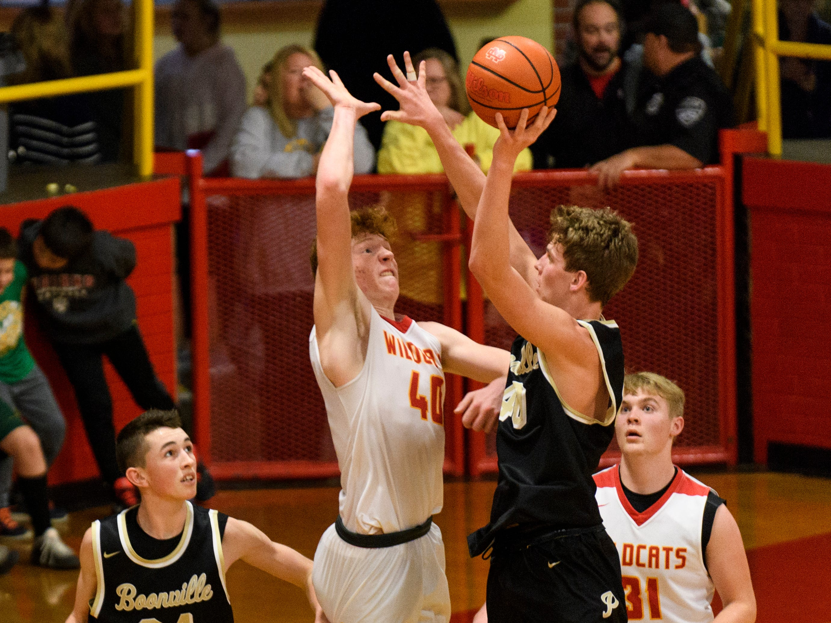 Mater Dei's Alex Money (40) blocks Boonville's Zeb Mills (40) from the net during the fourth quarter at Mater Dei High School in Evansville, Ind., Saturday, Jan. 5, 2019. The Wildcats defeated the Pioneers, 93-65.