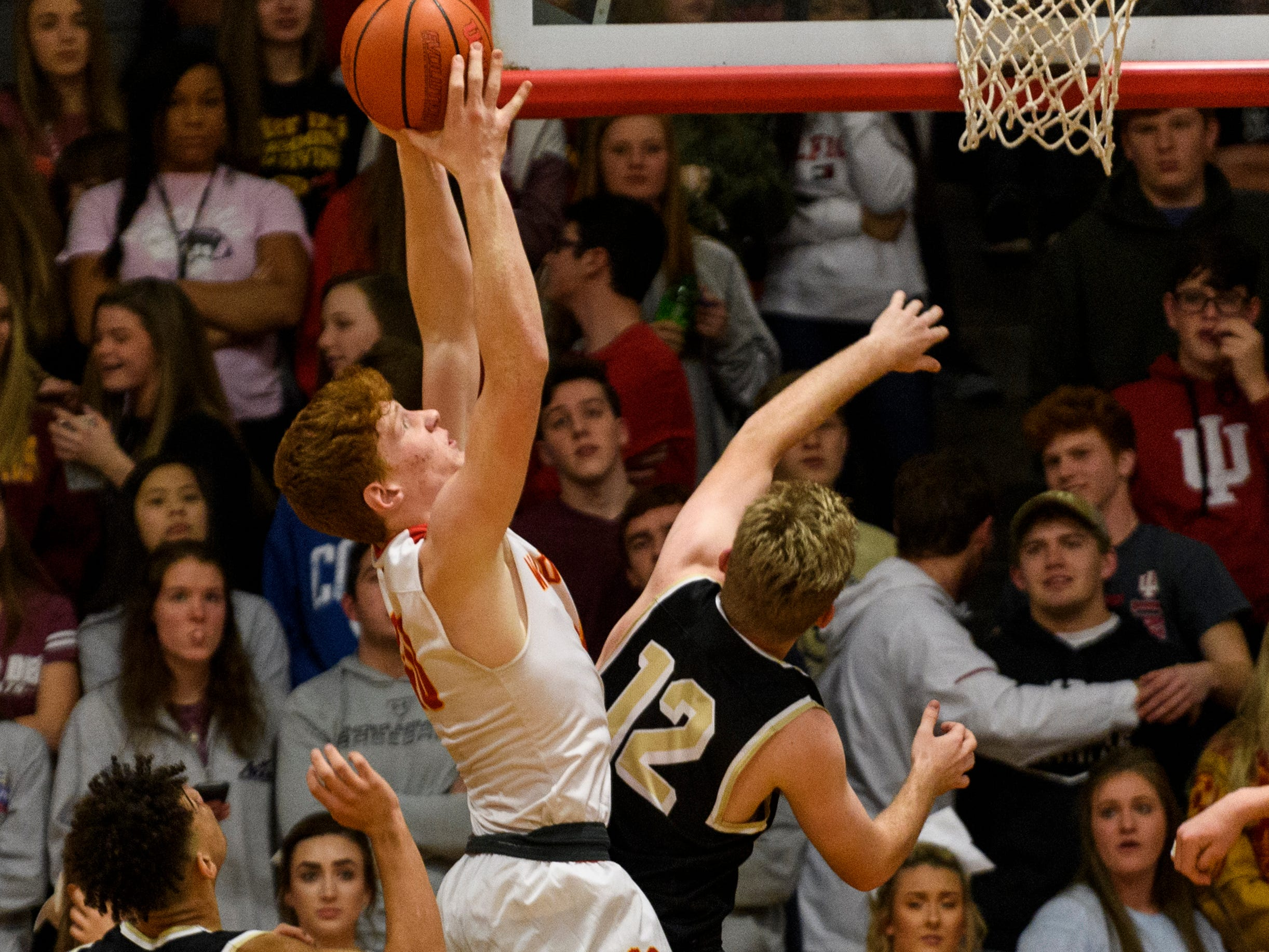 Mater Dei's Alex Money (40) gets the rebound before Boonville's Ben Meier (12) or Devin Mockobee (5) during the second quarter at Mater Dei High School in Evansville, Ind., Saturday, Jan. 5, 2019. The Wildcats defeated the Pioneers, 93-65.