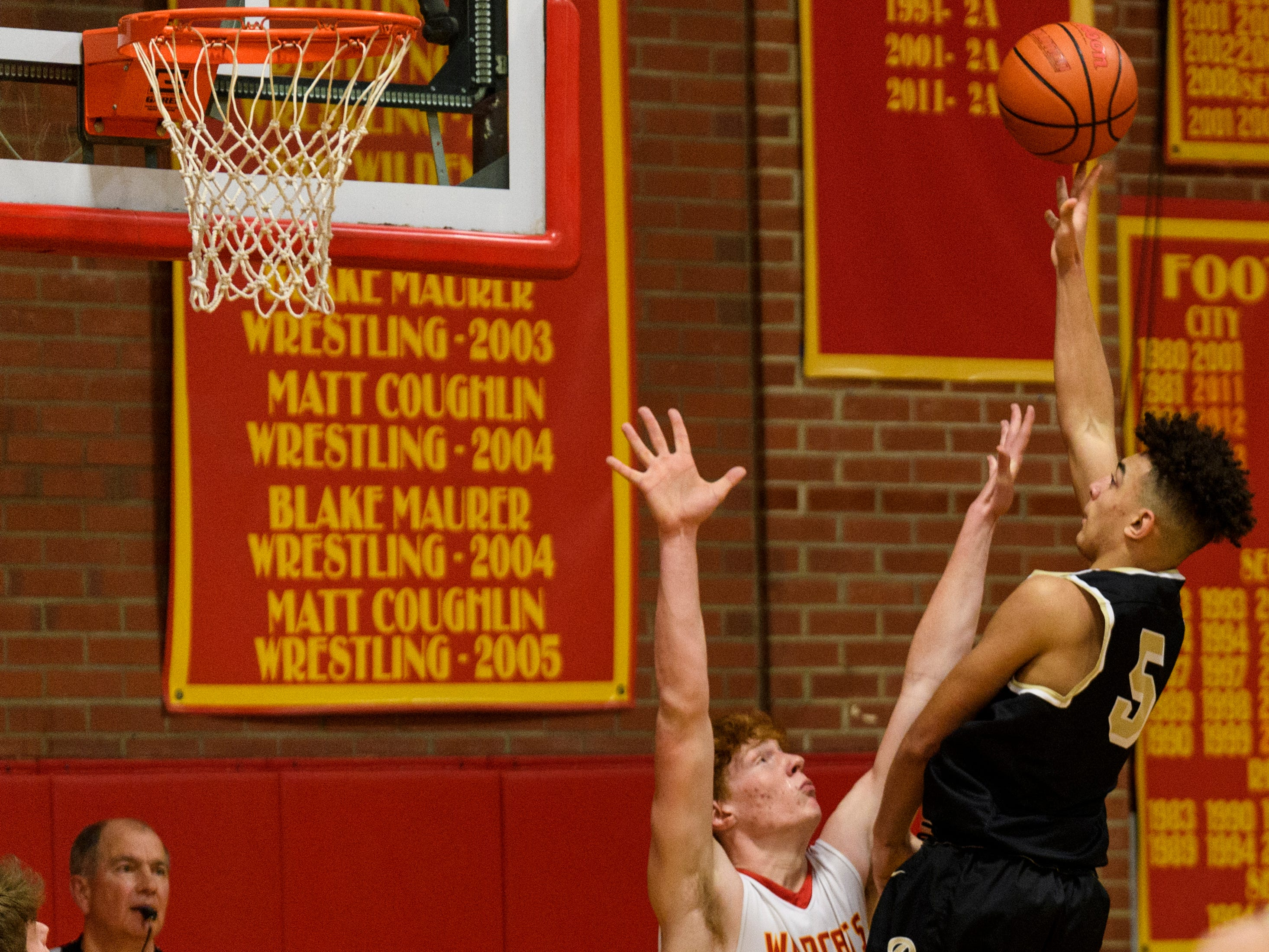 Mater Dei's Alex Money (40) attempts to block Boonville's Devin Mockobee (5) from the net during the second quarter at Mater Dei High School in Evansville, Ind., Saturday, Jan. 5, 2019. The Wildcats defeated the Pioneers, 93-65.