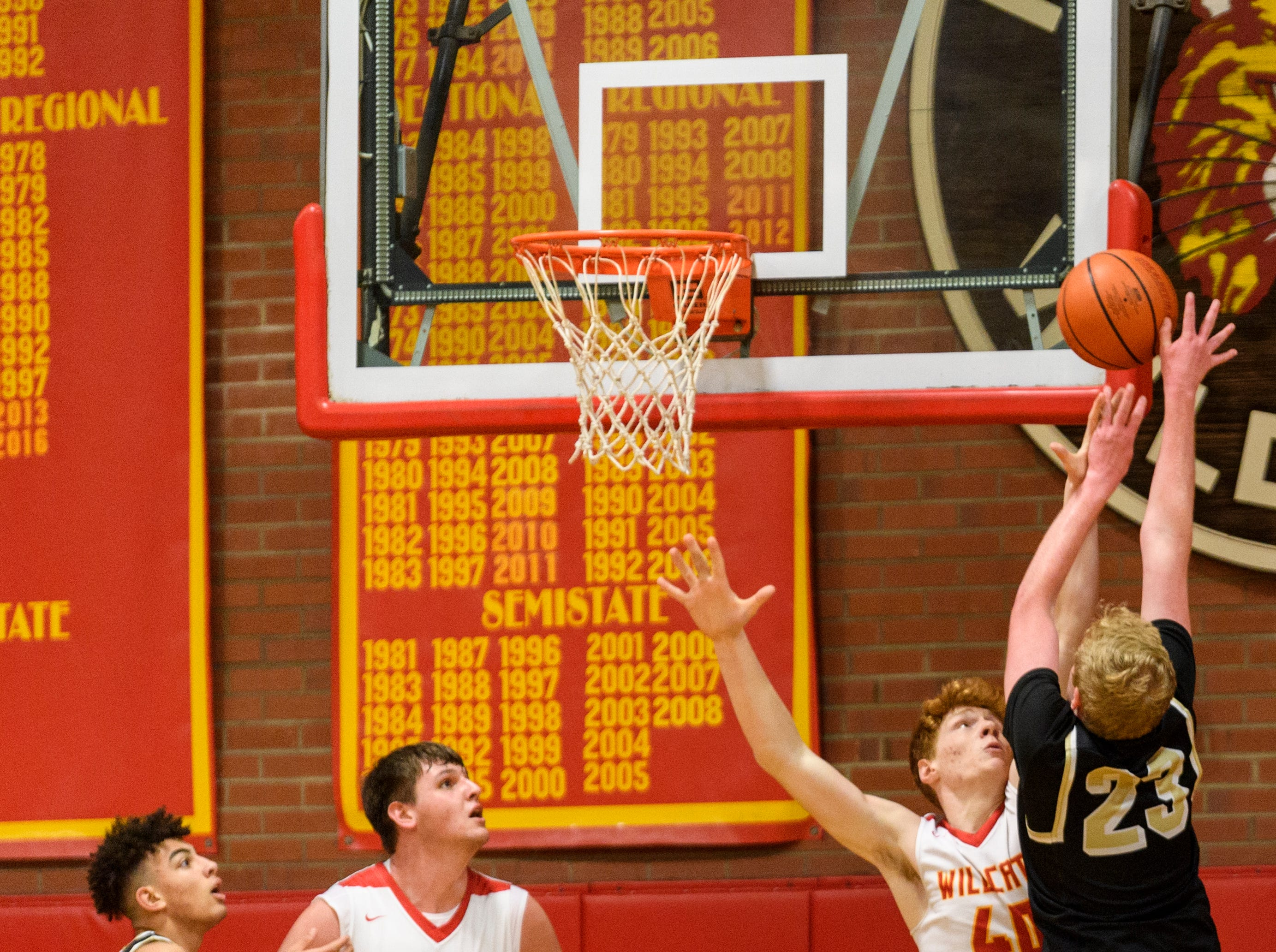 Mater Dei's Alex Money (40) blocks Boonville's Hunter Bruce (23) from the net as Mater Dei's Logan Carter (23) guards Boonville's Devin Mockobee (5) during the first quarter at Mater Dei High School in Evansville, Ind., Saturday, Jan. 5, 2019. The Wildcats defeated the Pioneers, 93-65.
