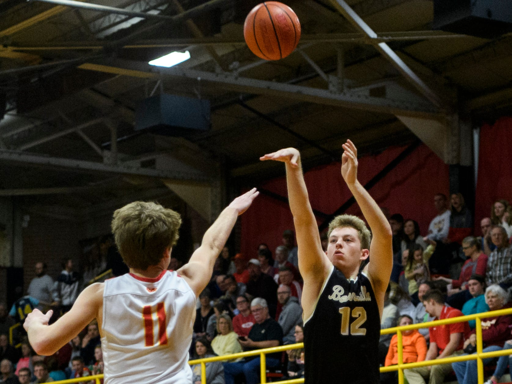Boonville's Ben Meier (12) attempts a three-pointer over Mater Dei's Dawson Caswell (11) in the second quarter at Mater Dei High School in Evansville, Ind., Saturday, Jan. 5, 2019. The Wildcats defeated the Pioneers, 93-65.