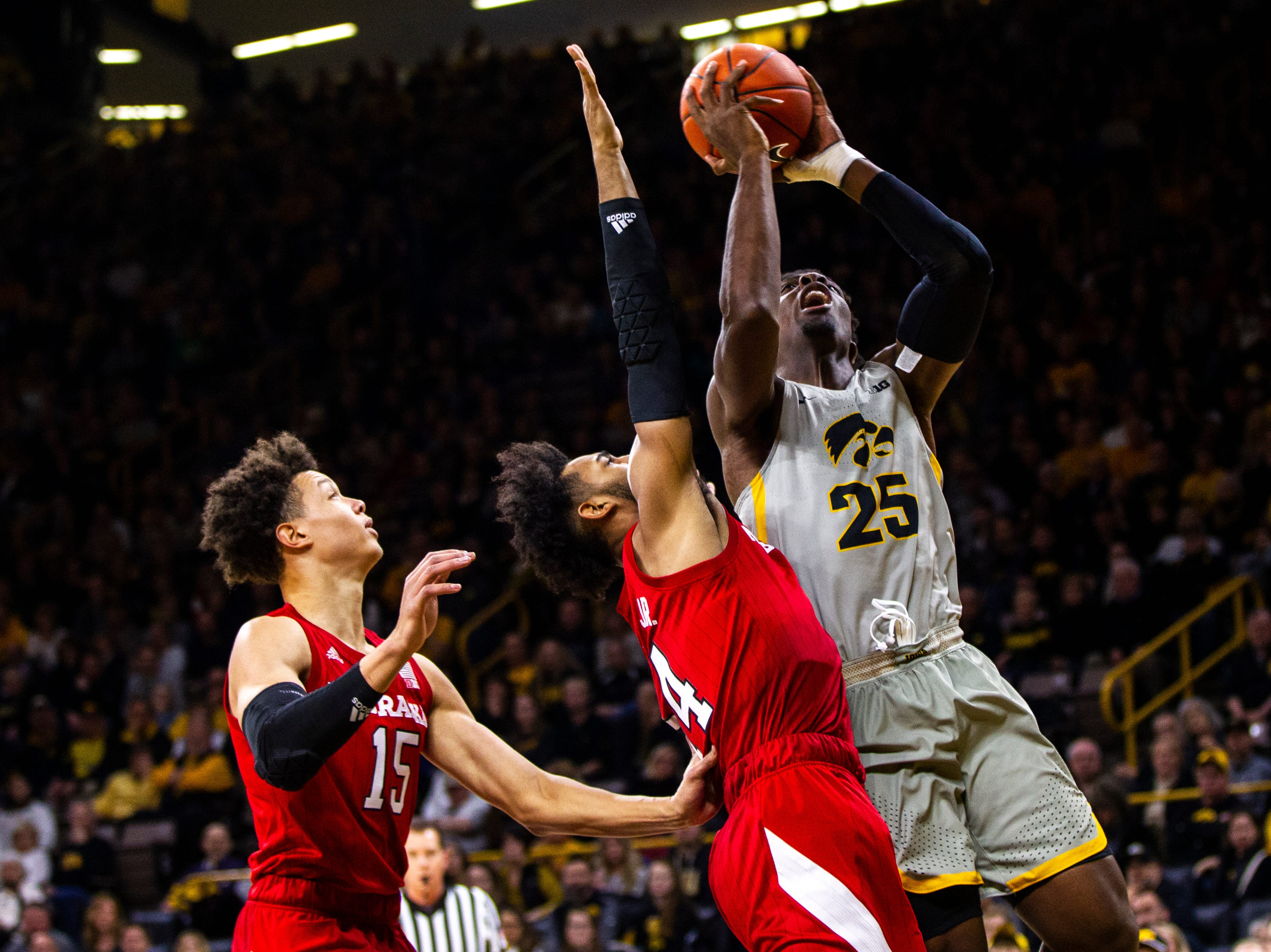 Iowa forward Tyler Cook (25) attempts a basket while getting defended by Nebraska forward Isaac Copeland Jr. (14) during a NCAA Big Ten Conference men's basketball game on Sunday, Jan. 6, 2019, at the Carver-Hawkeye Arena in Iowa City, Iowa.