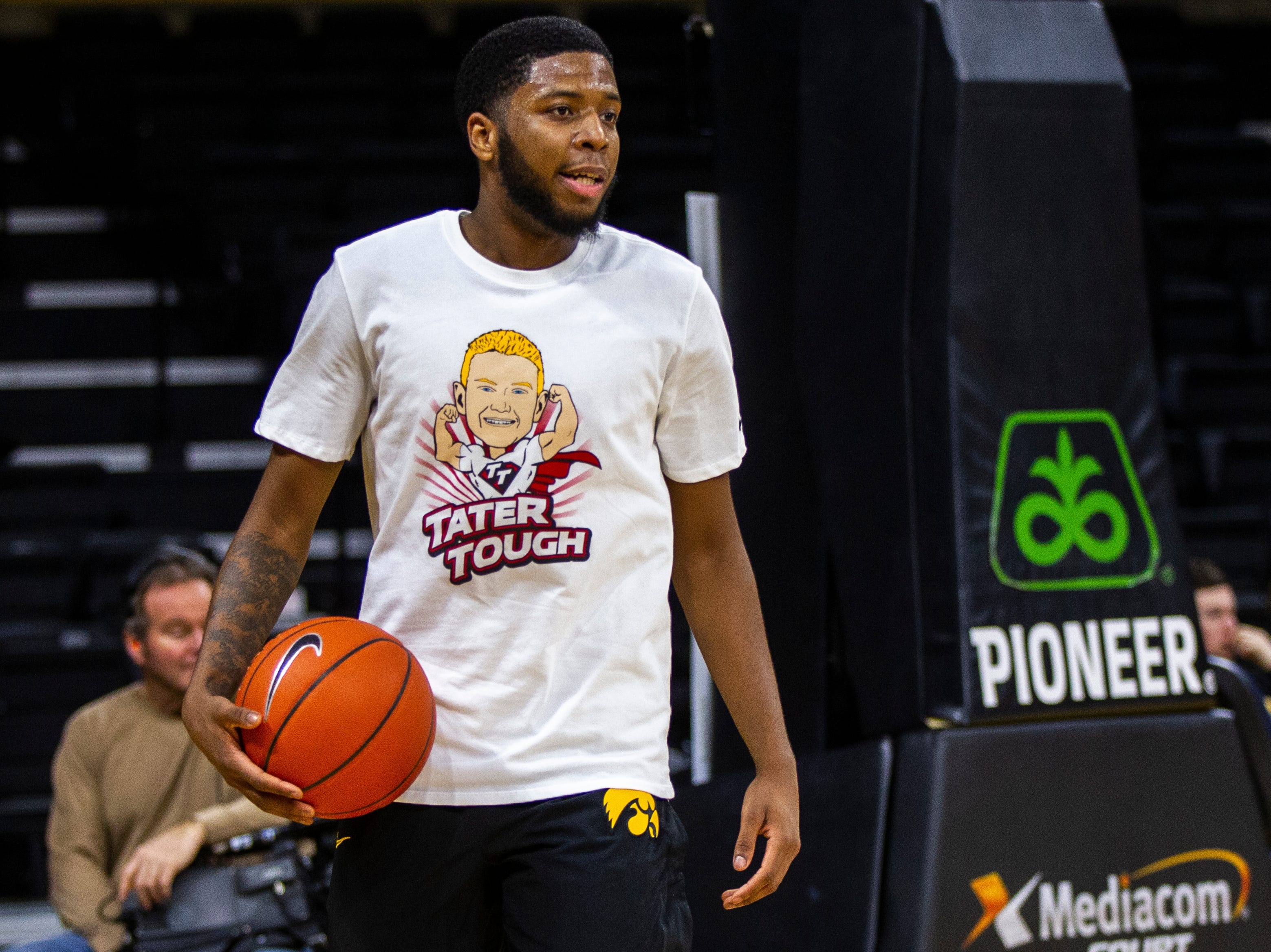 Iowa guard Isaiah Moss (4) warms up while wearing a shirt featuring a logo for Tate Schaefer, an 11-year-old from Williamsburg who has a tumor in his brain before a NCAA Big Ten Conference men's basketball game on Sunday, Jan. 6, 2019, at the Carver-Hawkeye Arena in Iowa City, Iowa.