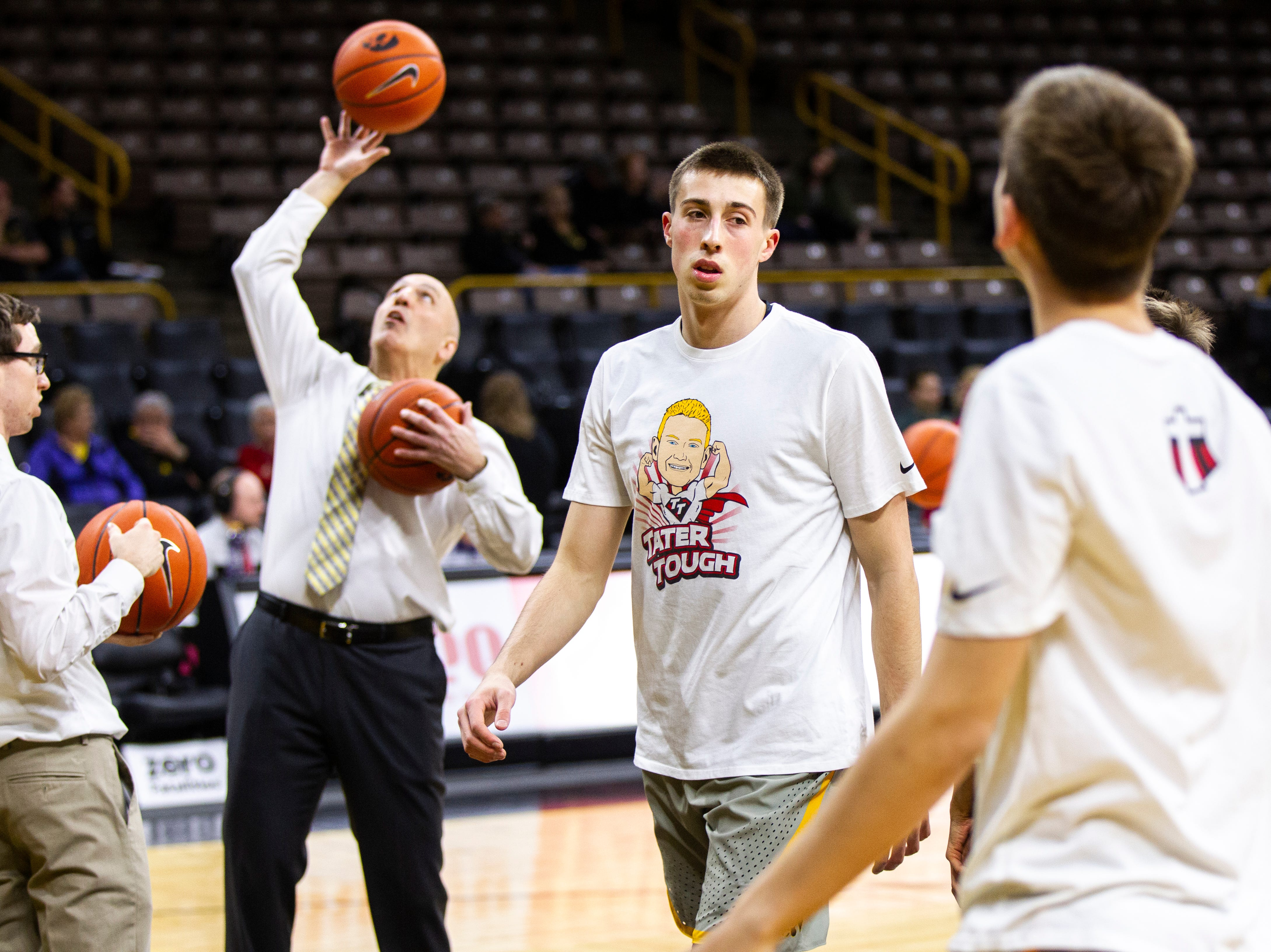 Iowa guard Joe Wieskamp (10) warms up while wearing a shirt featuring a logo for Tate Schaefer, an 11-year-old from Williamsburg who has a tumor in his brain before a NCAA Big Ten Conference men's basketball game on Sunday, Jan. 6, 2019, at the Carver-Hawkeye Arena in Iowa City, Iowa.