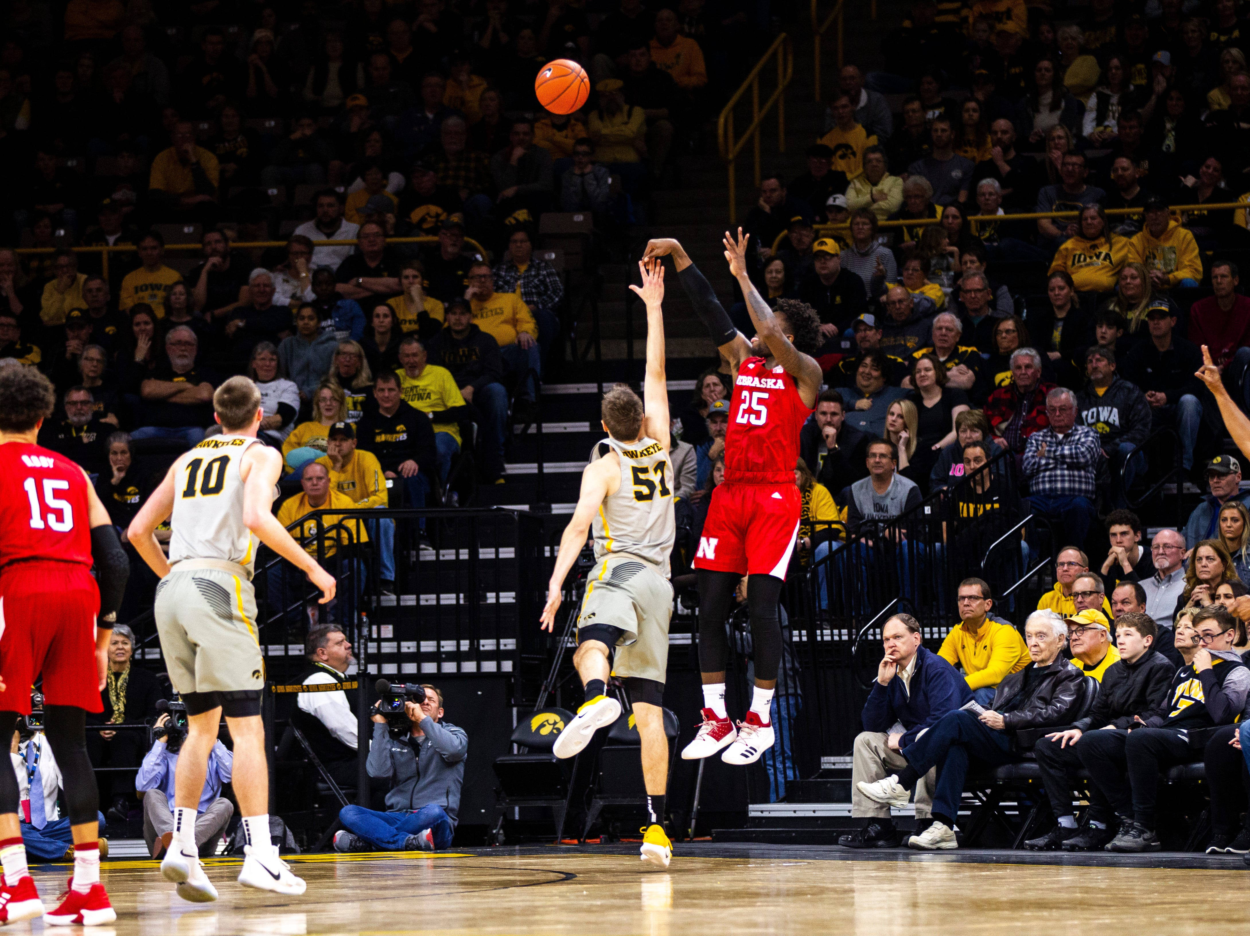 Iowa forward Nicholas Baer (51) gets called for a foul on Nebraska guard Nana Akenten (25) as he shoots a 3-point basket during a NCAA Big Ten Conference men's basketball game on Sunday, Jan. 6, 2019, at the Carver-Hawkeye Arena in Iowa City, Iowa.