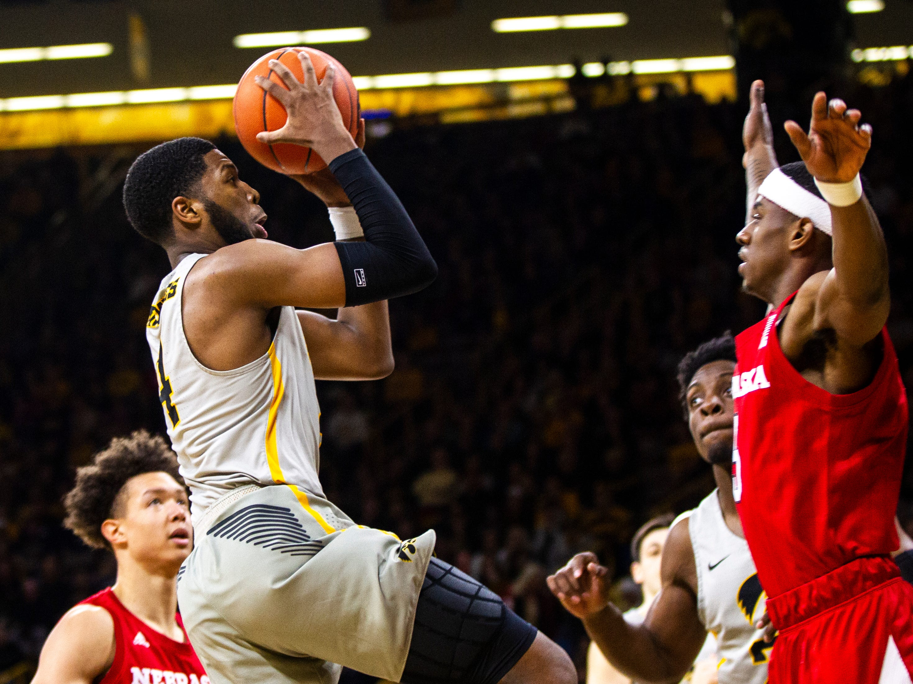 Iowa guard Isaiah Moss (4) makes a basket past Nebraska guard Glynn Watson Jr. (5) during a NCAA Big Ten Conference men's basketball game on Sunday, Jan. 6, 2019, at the Carver-Hawkeye Arena in Iowa City, Iowa.
