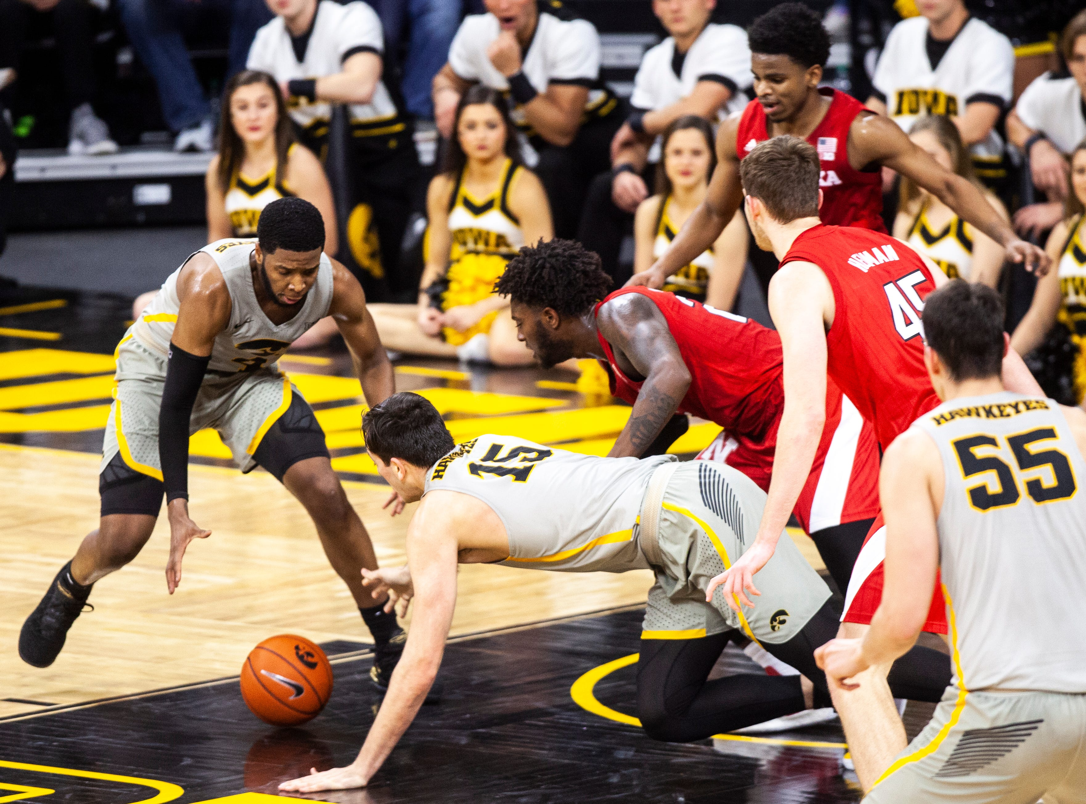 Iowa guard Isaiah Moss (4) and Iowa forward Ryan Kriener (15) dive for a loose ball during a NCAA Big Ten Conference men's basketball game on Sunday, Jan. 6, 2019, at the Carver-Hawkeye Arena in Iowa City, Iowa.