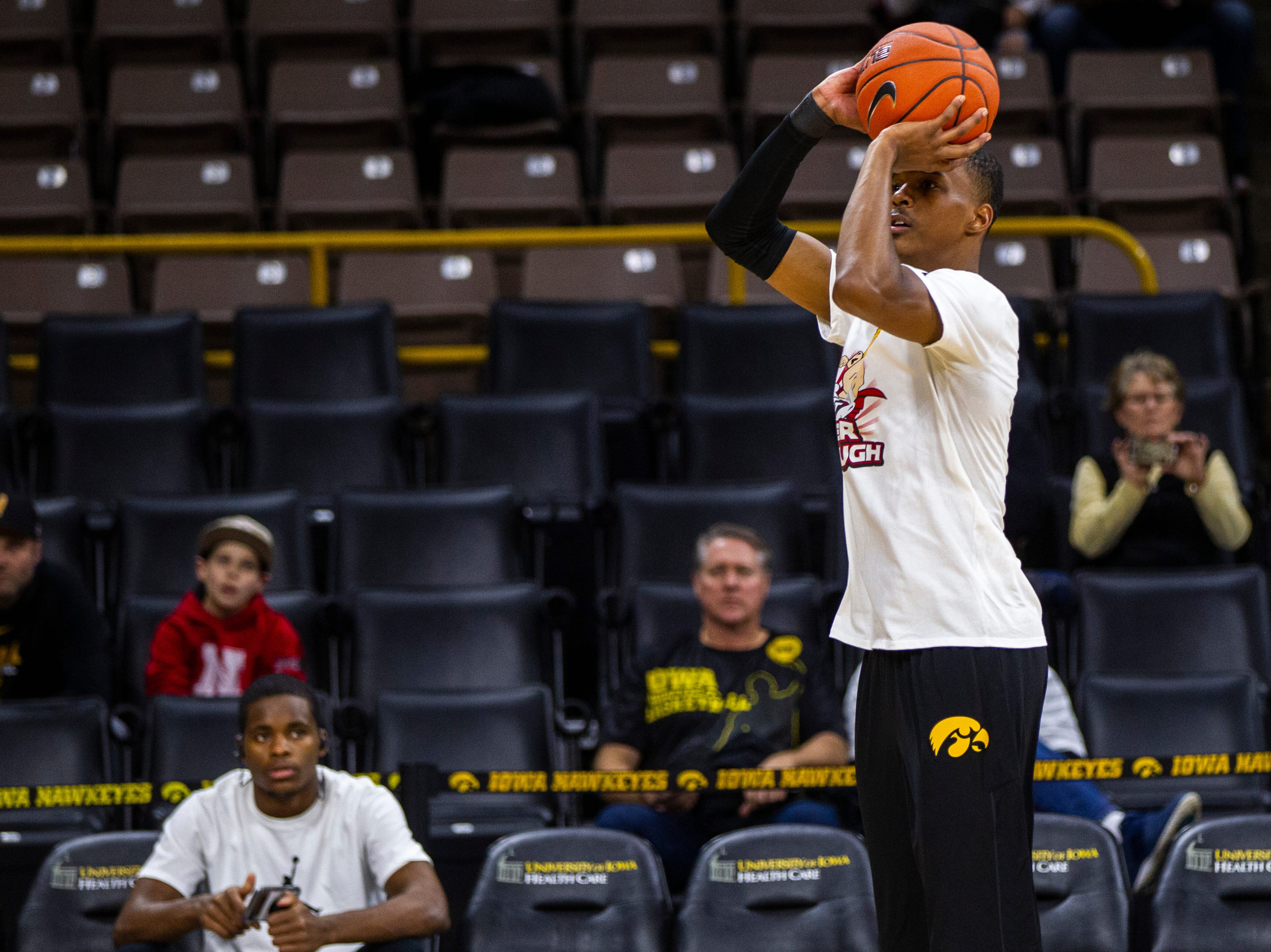 Iowa guard Maishe Dailey (1) warms up while wearing a shirt featuring a logo for Tate Schaefer, an 11-year-old from Williamsburg who has a tumor in his brain before a NCAA Big Ten Conference men's basketball game on Sunday, Jan. 6, 2019, at the Carver-Hawkeye Arena in Iowa City, Iowa.